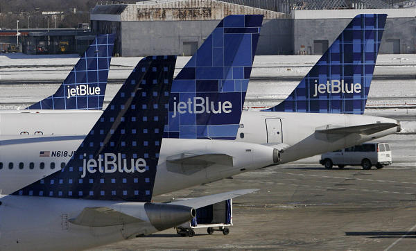 JetBlue planes wait at terminal gates at JFK Airport in New York. JetBlue's CEO stepped down about a year ago.