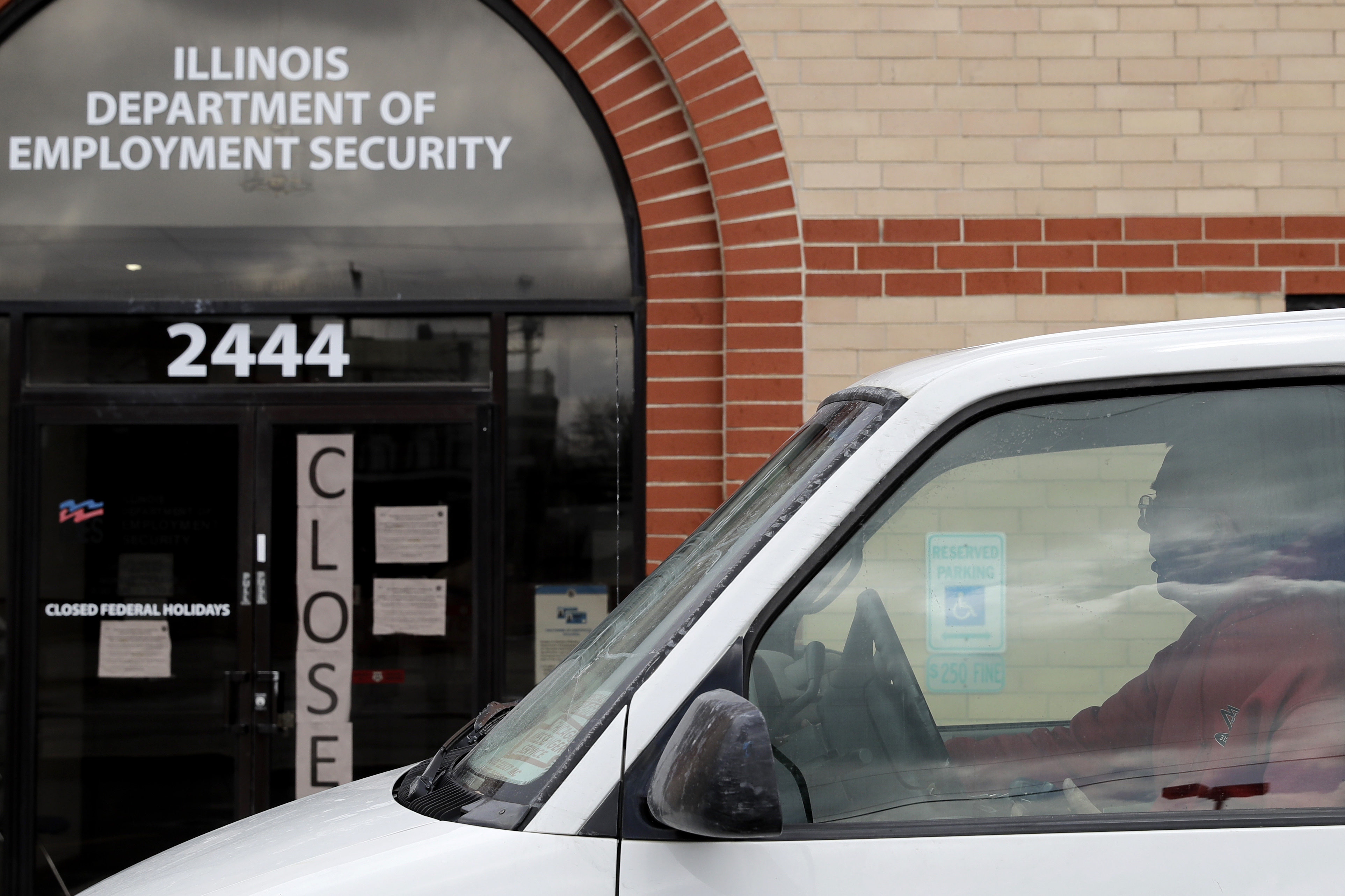 A man looks at the closed sign in front of Illinois Department of Employment Security in Chicago, Wednesday, April 15, 2020.