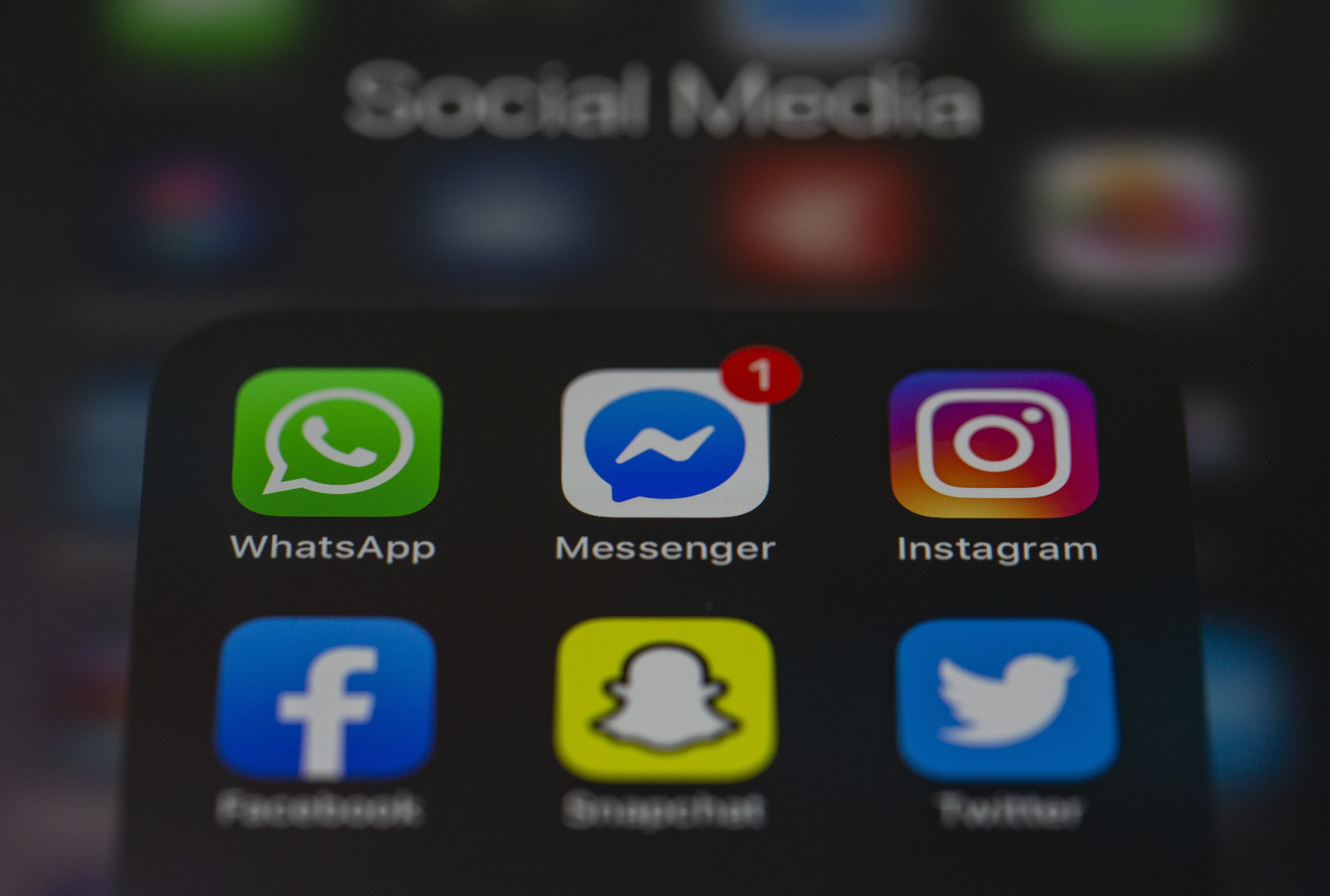 The Facebook Messenger icon on a smartphone screen with other social media apps.