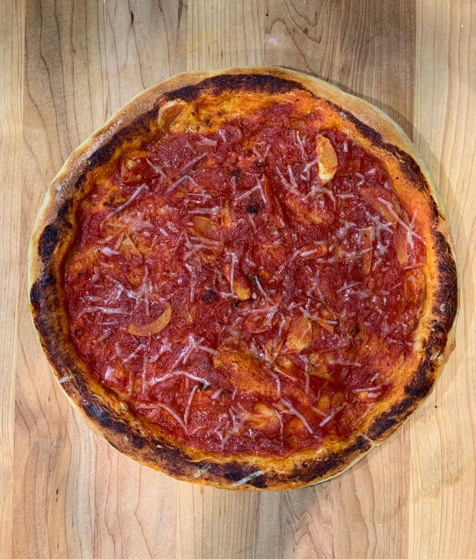 Red circular pizza with visible garlic slices and no cheese