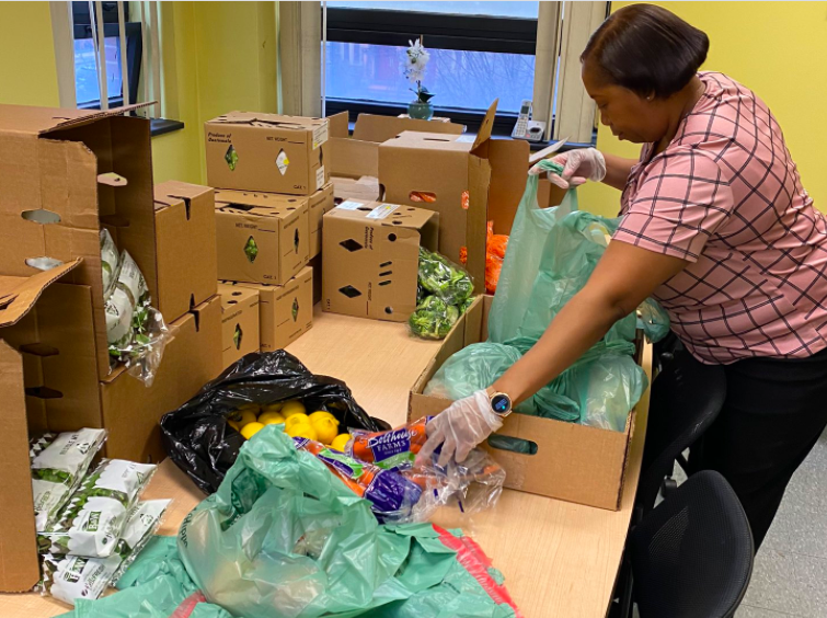 A Technology High School volunteer prepares a bag of food in Newark.