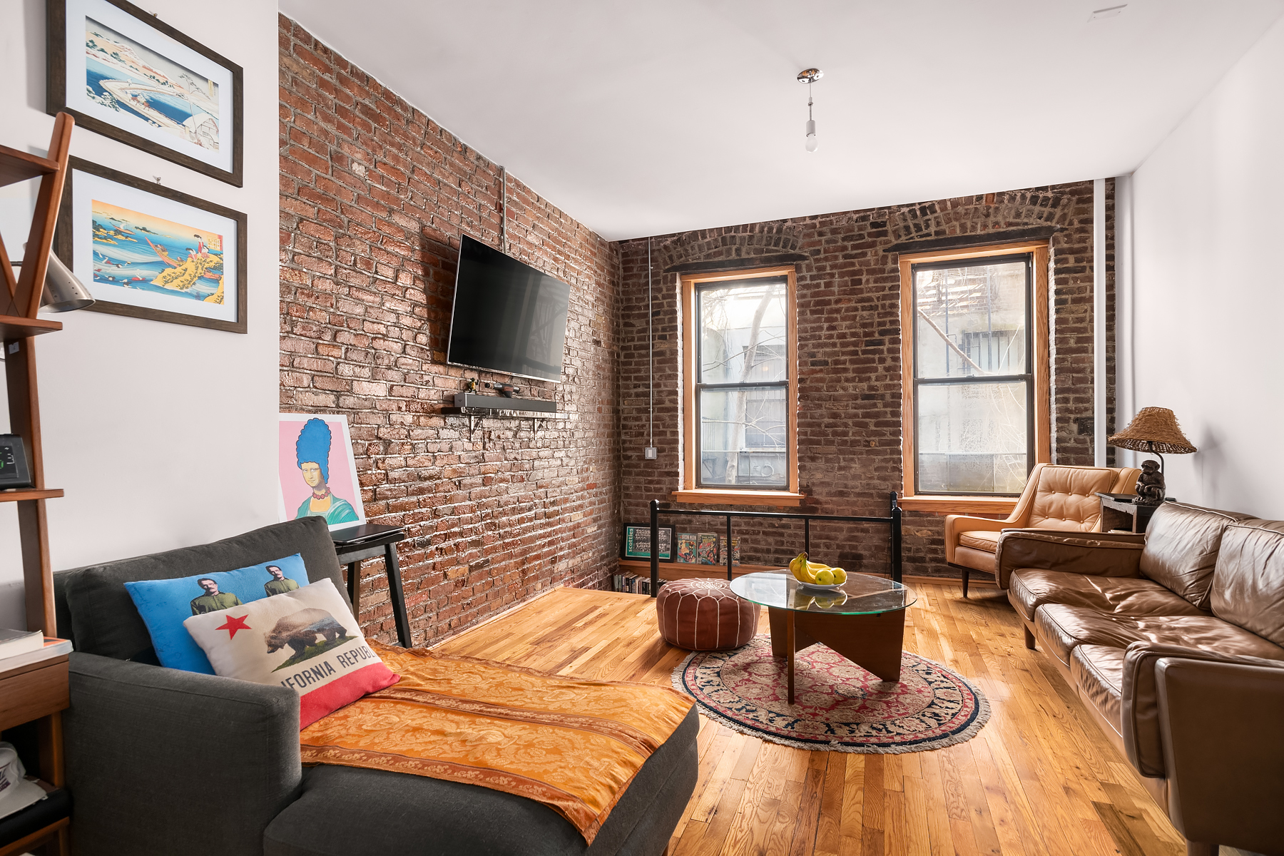 A living area with exposed brick, hardwood floors, and a brown leather couch.