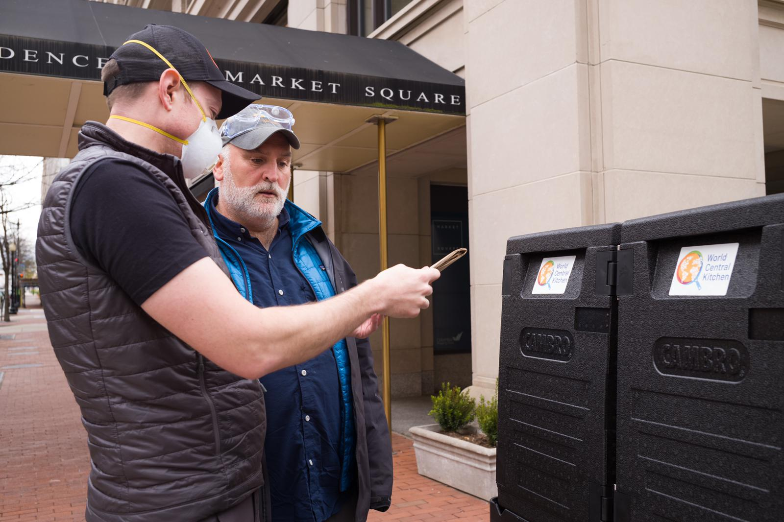 Two men looking at an ipad on the street, one wearing a face mask