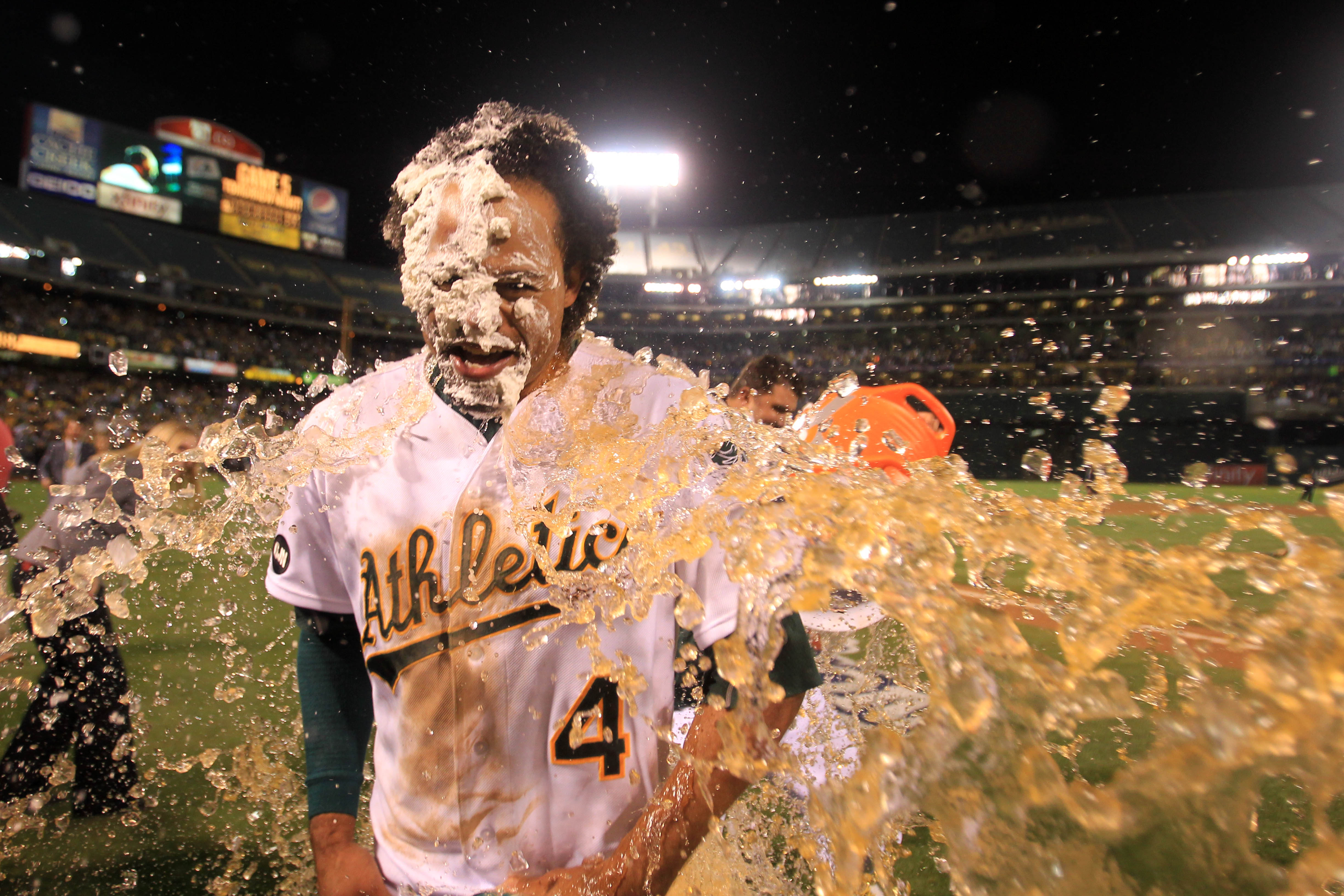 Oakland Athletics' Coco Crisp (4) smiles with his face covered with the ritual whipped cream pie as he gets doused with gatorade during the celebration on his walk-off single against the Detroit Tigers in the ninth inning of their Game 4 of the American L