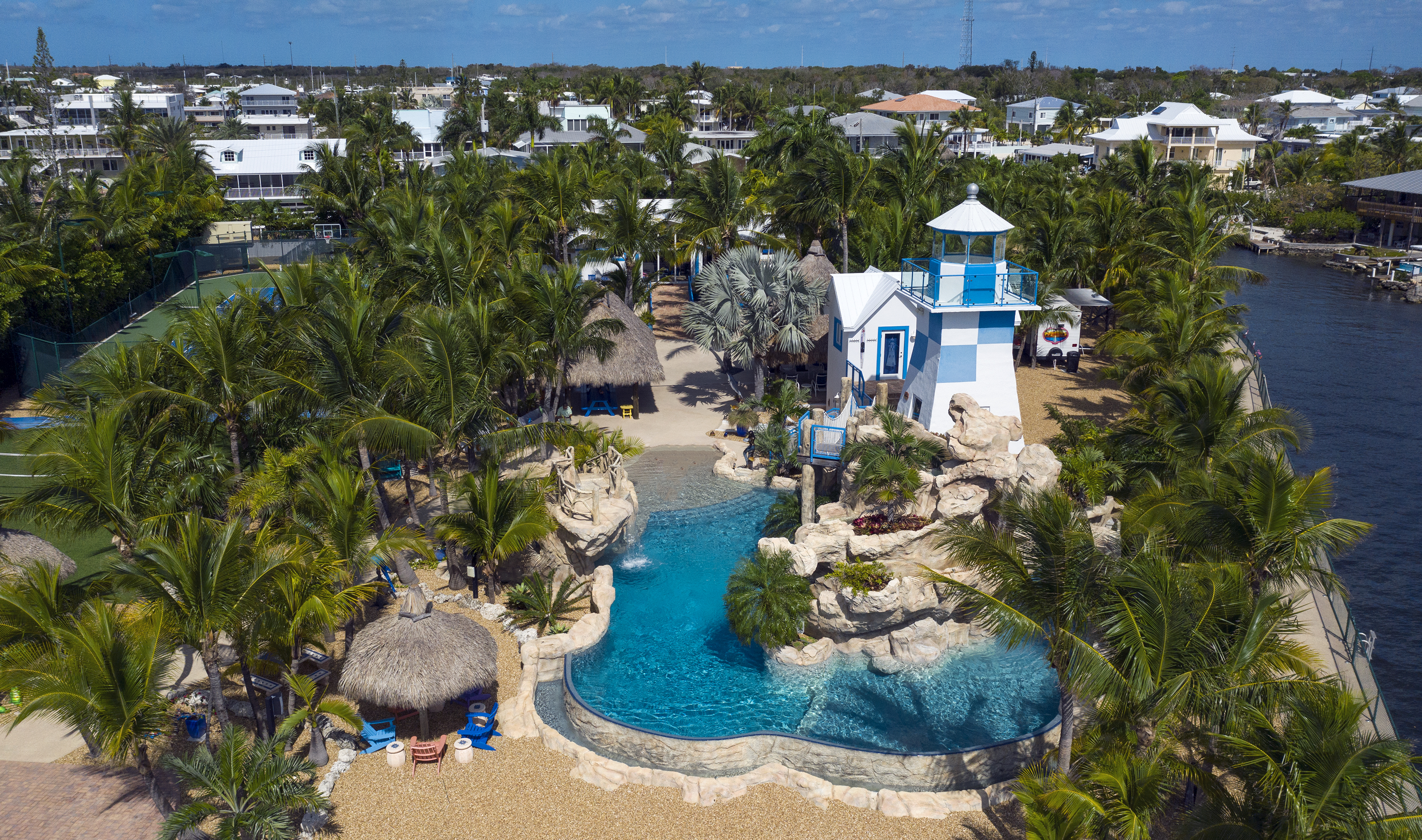An aerial view of a resort-type pool, with palm trees and a blue and white lighthouse surrounding the water.