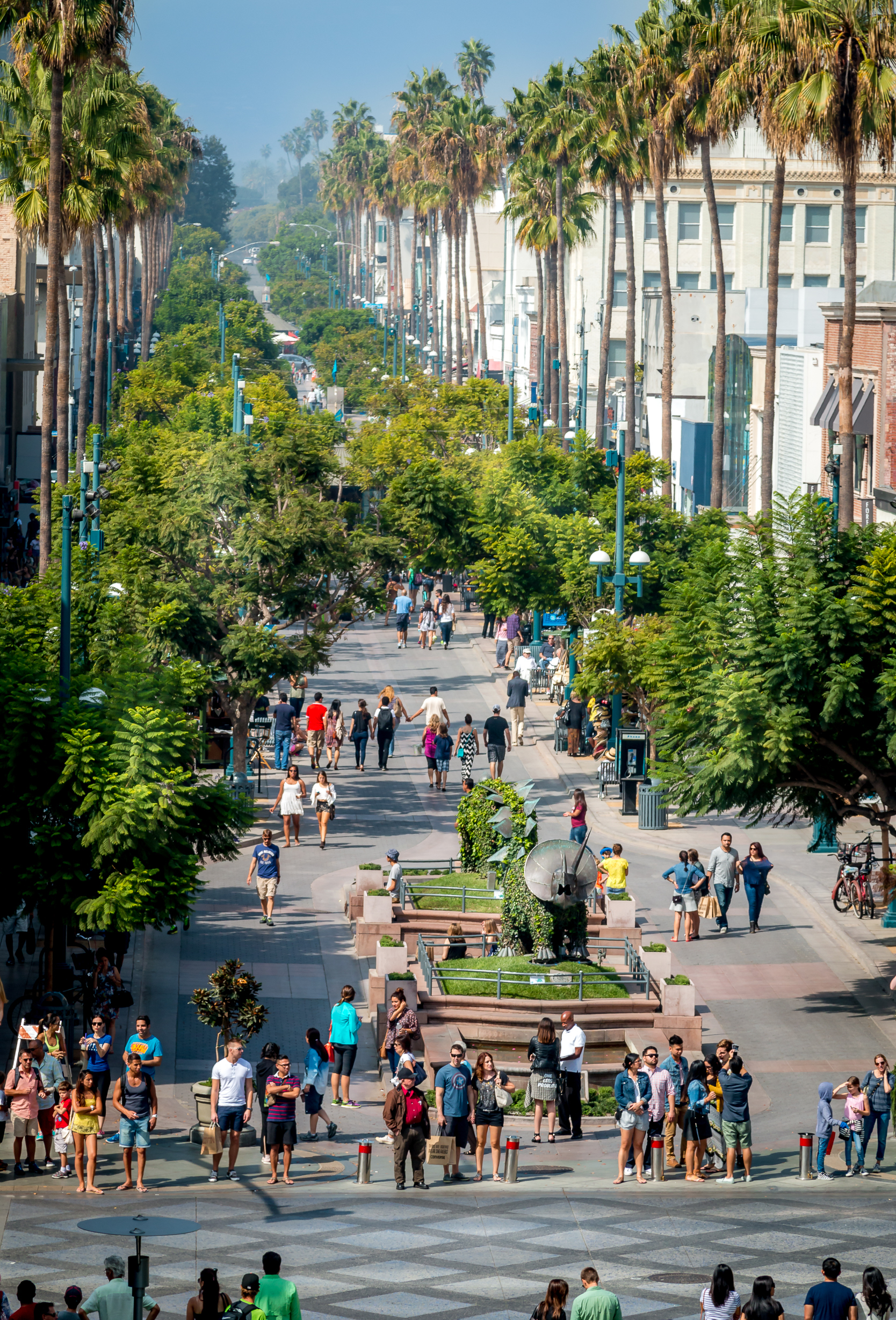 Aerial view of a wide, tree-lined street where lots of people are walking.