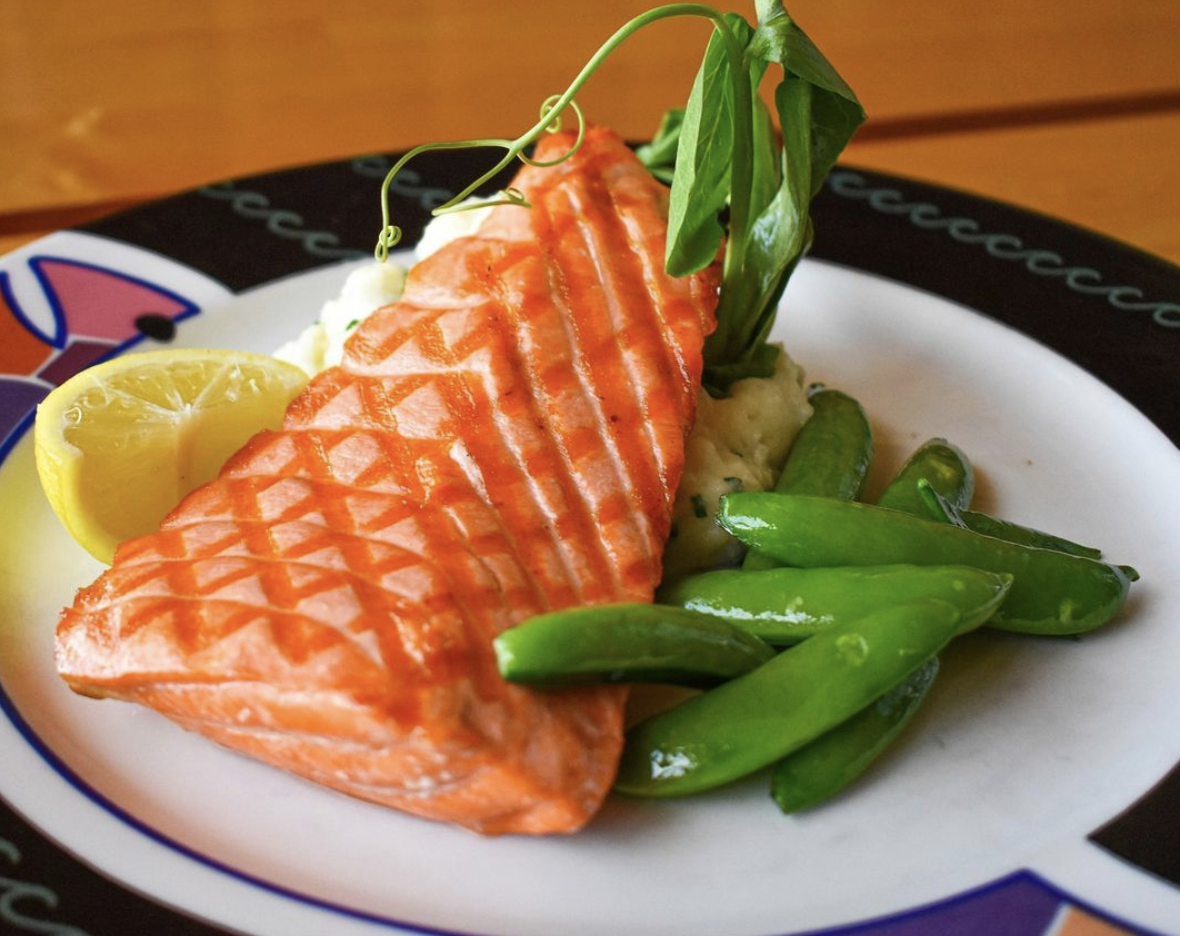 Chargrilled salmon on a white plate with a side of pea pods and a slice of lemon