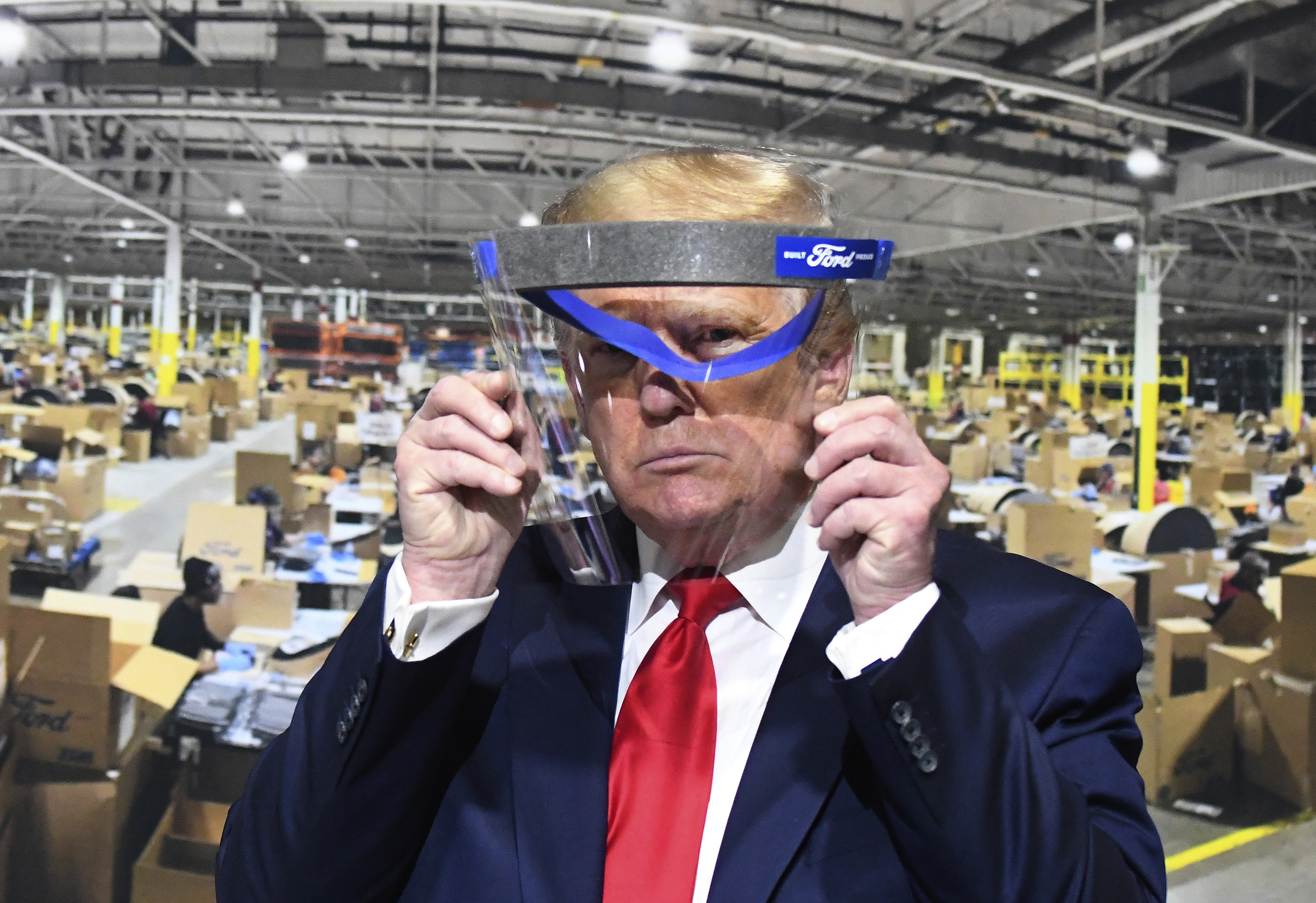 President Donald Trump looks through a face shield, in front of a poster of the manufacturing of the shields, while touring Ford Motor Co.'s Rawsonville Components Plant in Ypsilanti, Michigan on Thursday, May 21, 2020.