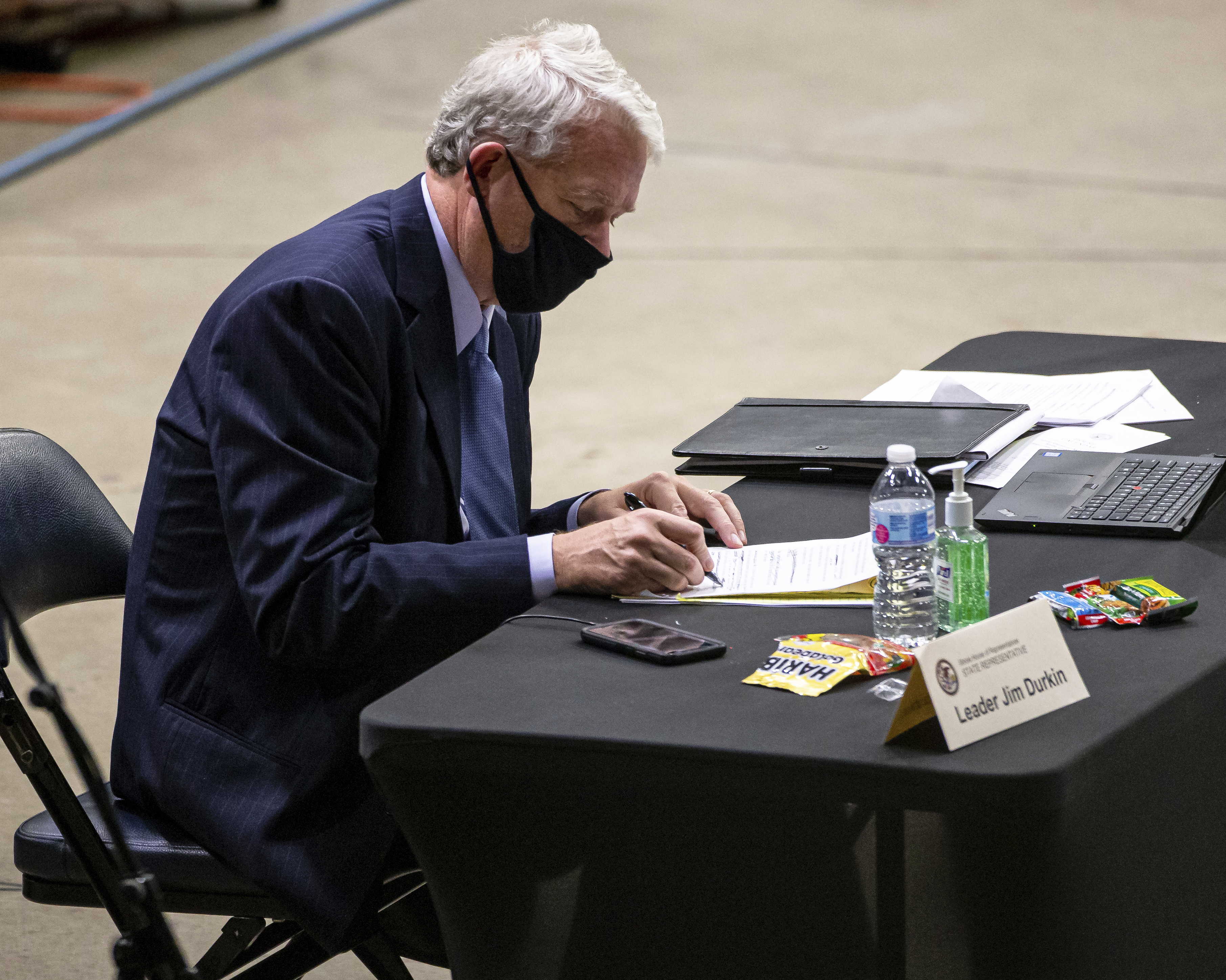 Illinois House Republican Leader Jim Durkin, R-Western Springs, takes notes at his desk — spaced six feet from the desks of other lawkmakers — during a legislative session on Saturday in Springfield.