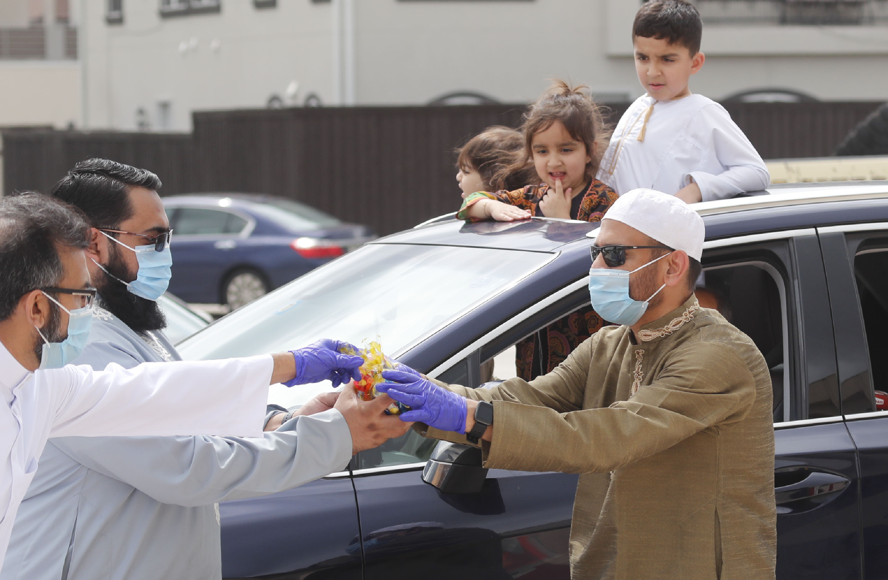 Children look on from a sunroof as organizers prepared to give them candy during an Eid al-Fitr drive through celebration outside a closed mosque in Plano, Texas, Sunday, May 24, 2020. Many Muslims in America are navigating balancing religious and social rituals with concerns over the virus as they look for ways to capture the Eid spirit this weekend.