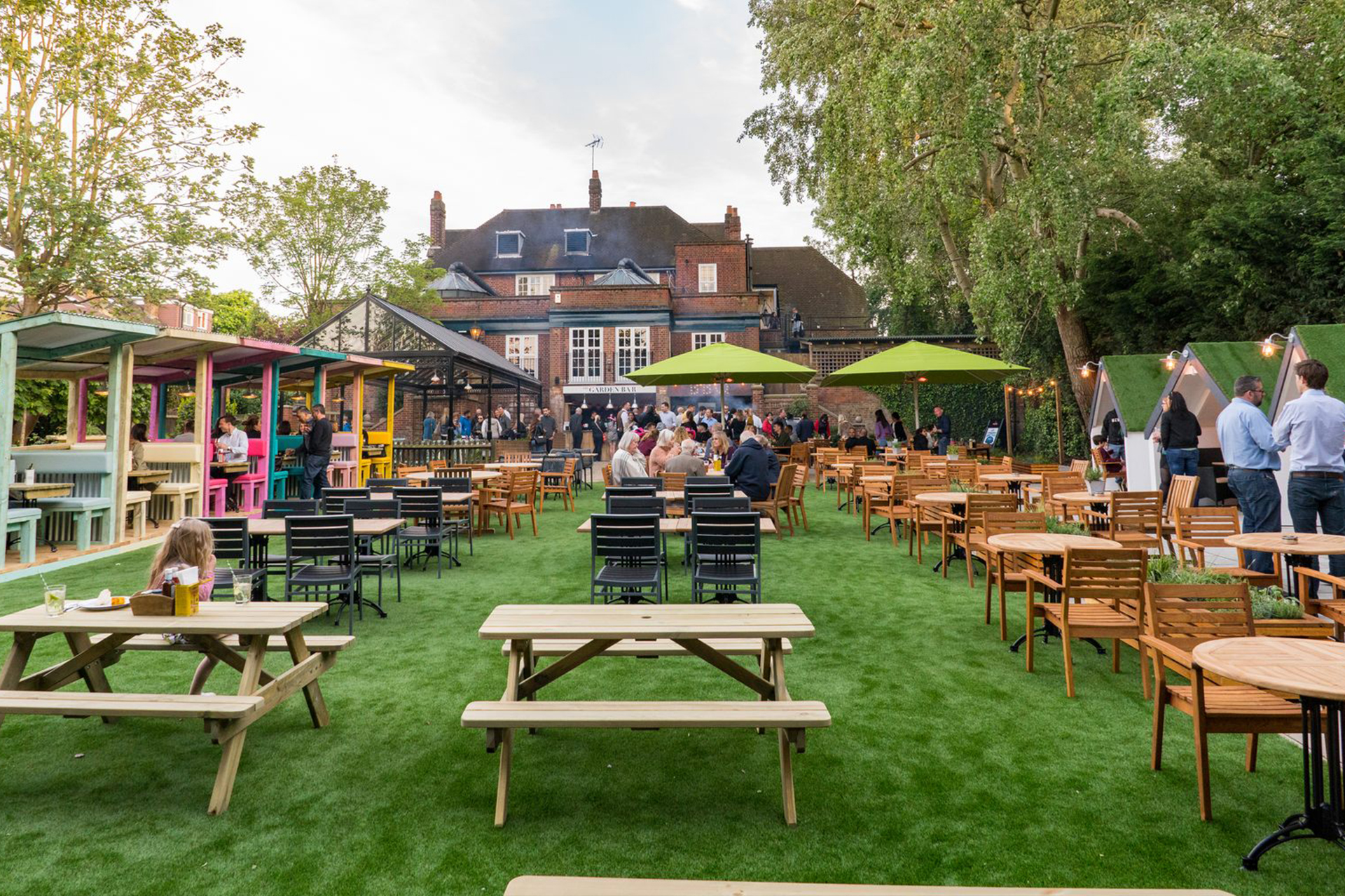A grass beer garden with picnic tables at a London pub