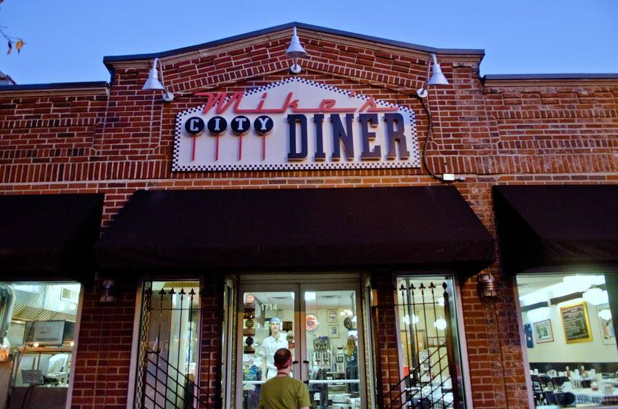 Brick exterior of a casual restaurant with white, black, and red signage reading Mike's City Diner