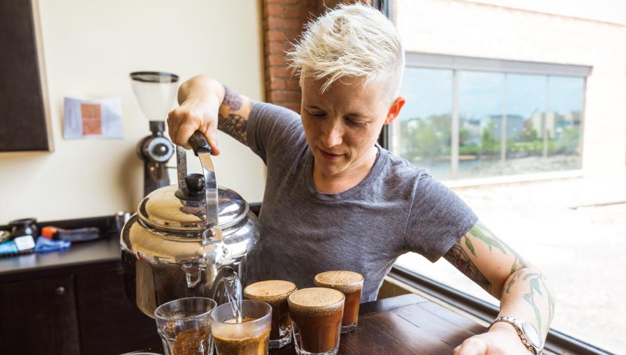 A white woman with short blonde hair pours coffee into short glasses.