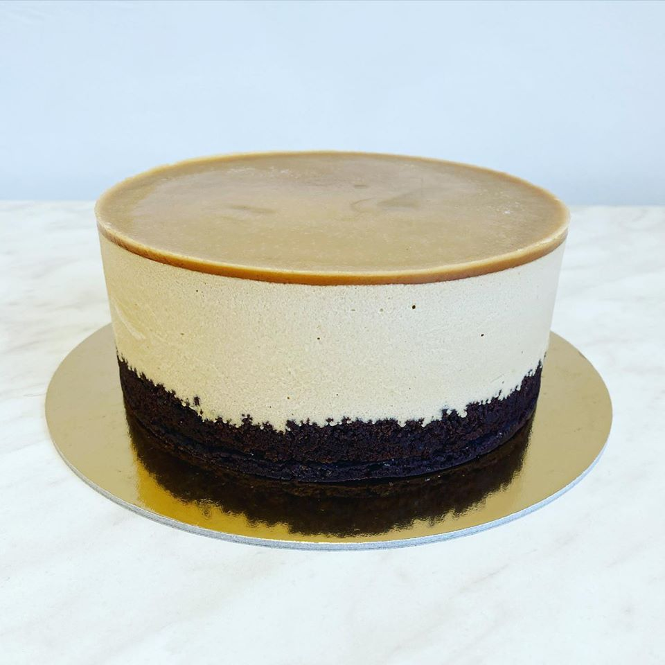 A cake with bare layers of chocolate, buttercream, and a salted caramel disk on top