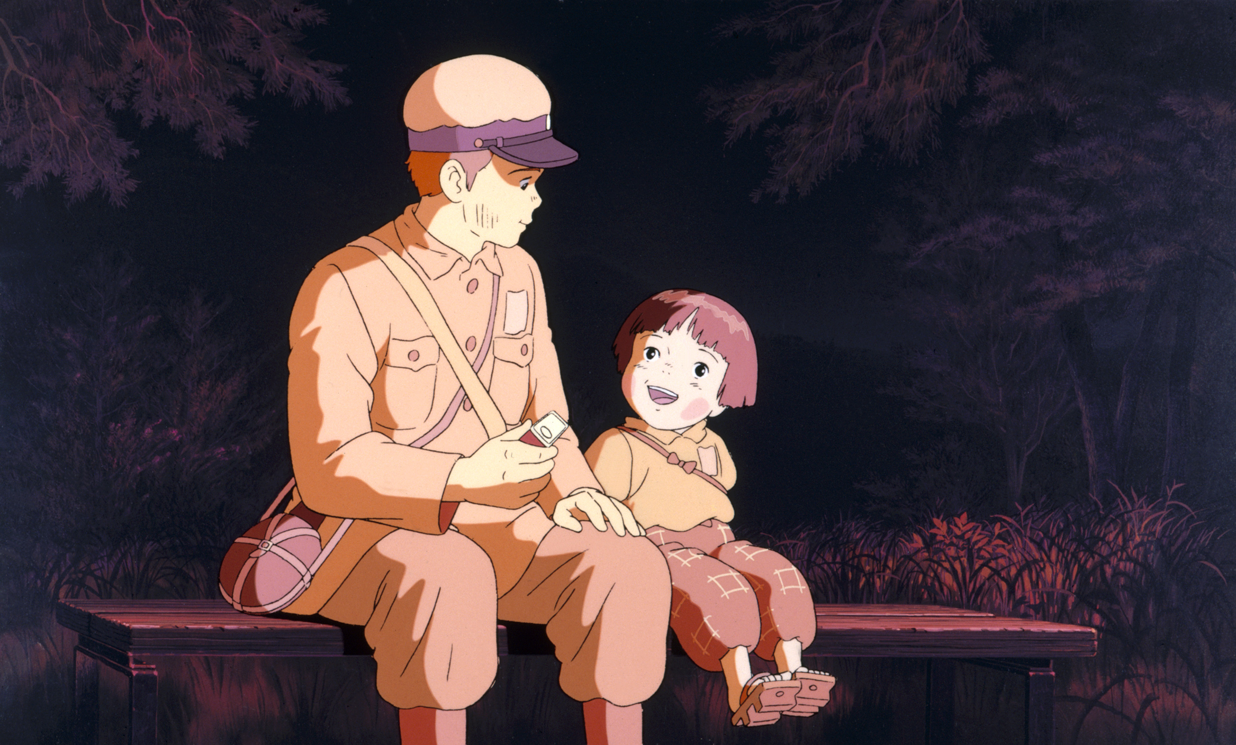 A young Japanese boy and his younger sister sit on a bench together in Grave of the Fireflies