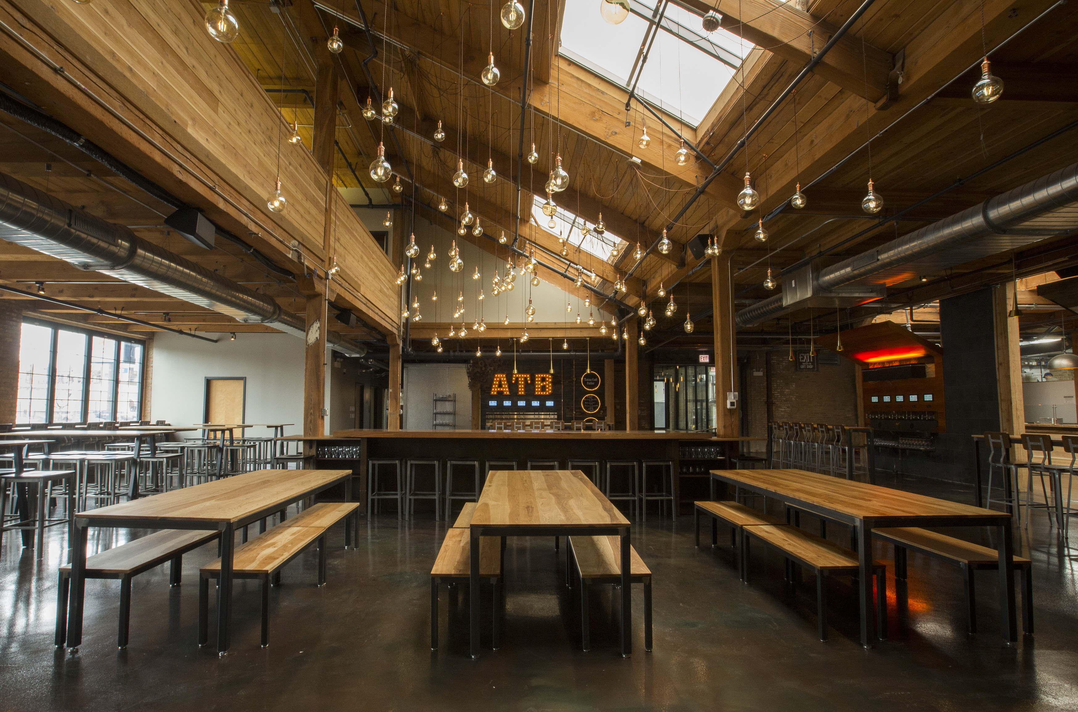 A beer hall with an industrial look an string lights.