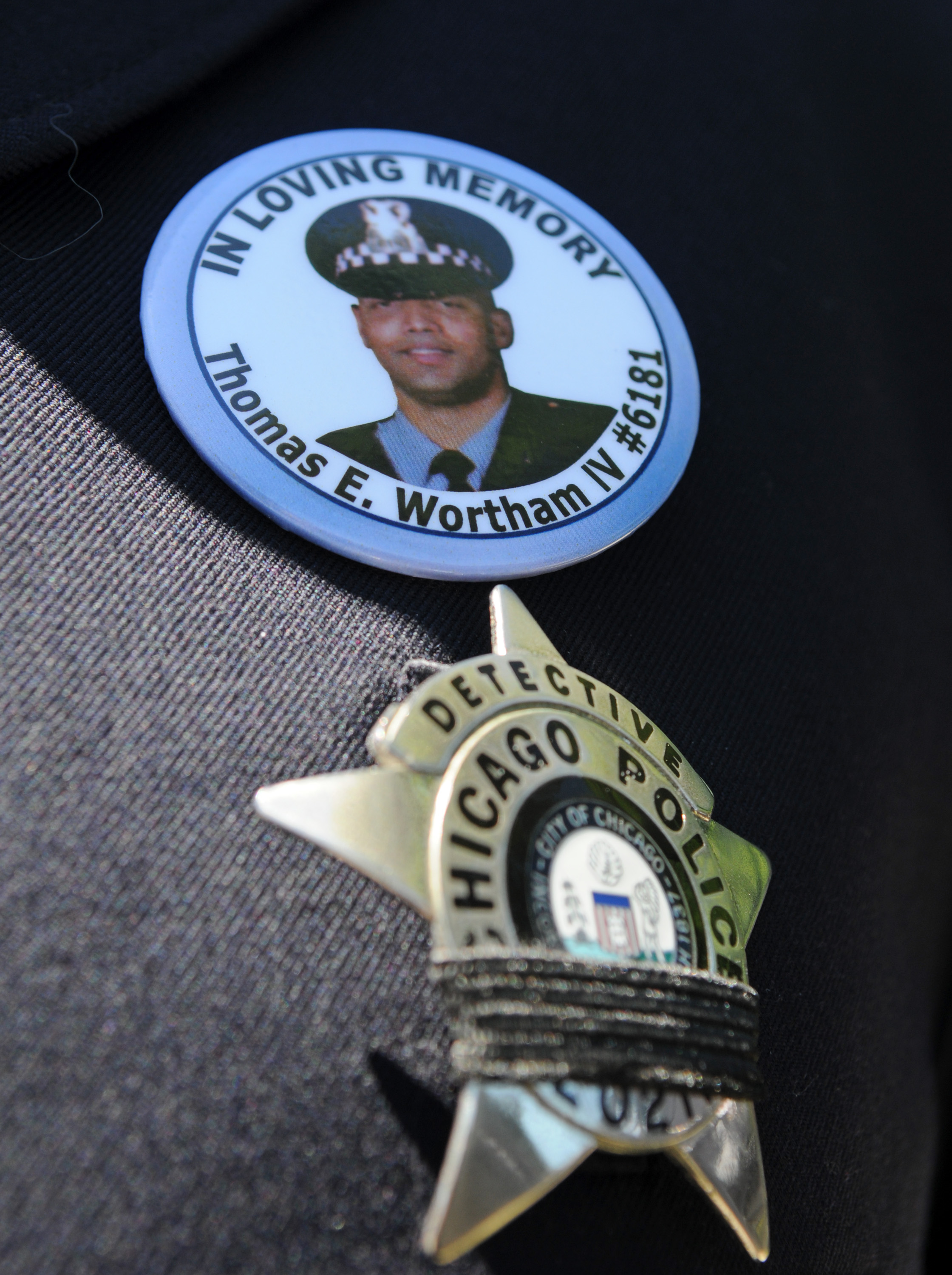 A Chicago Police officer wears a button in memory of fellow Officer Thomas Wortham IV at his funeral ten years ago.