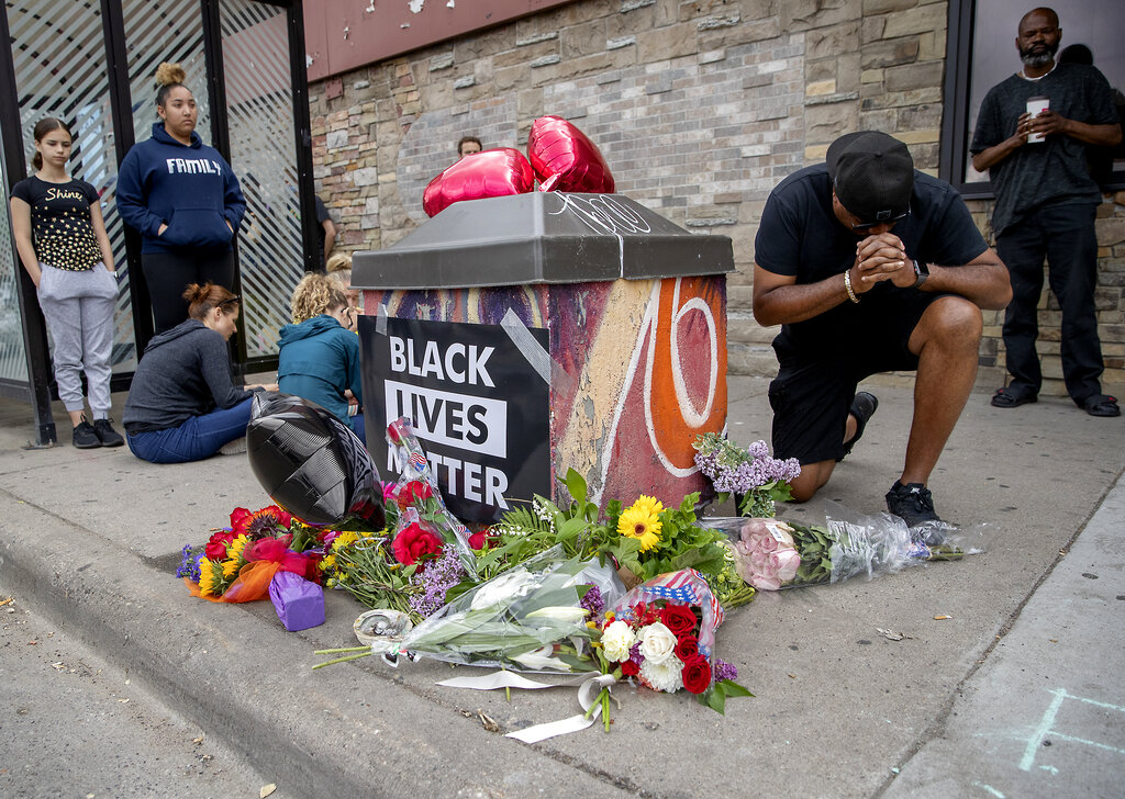 People gather and pray around a makeshift memorial, Tuesday, May 26, 2020, in Minneapolis, near the site where a black man, who was taken into police custody the day before, later died.