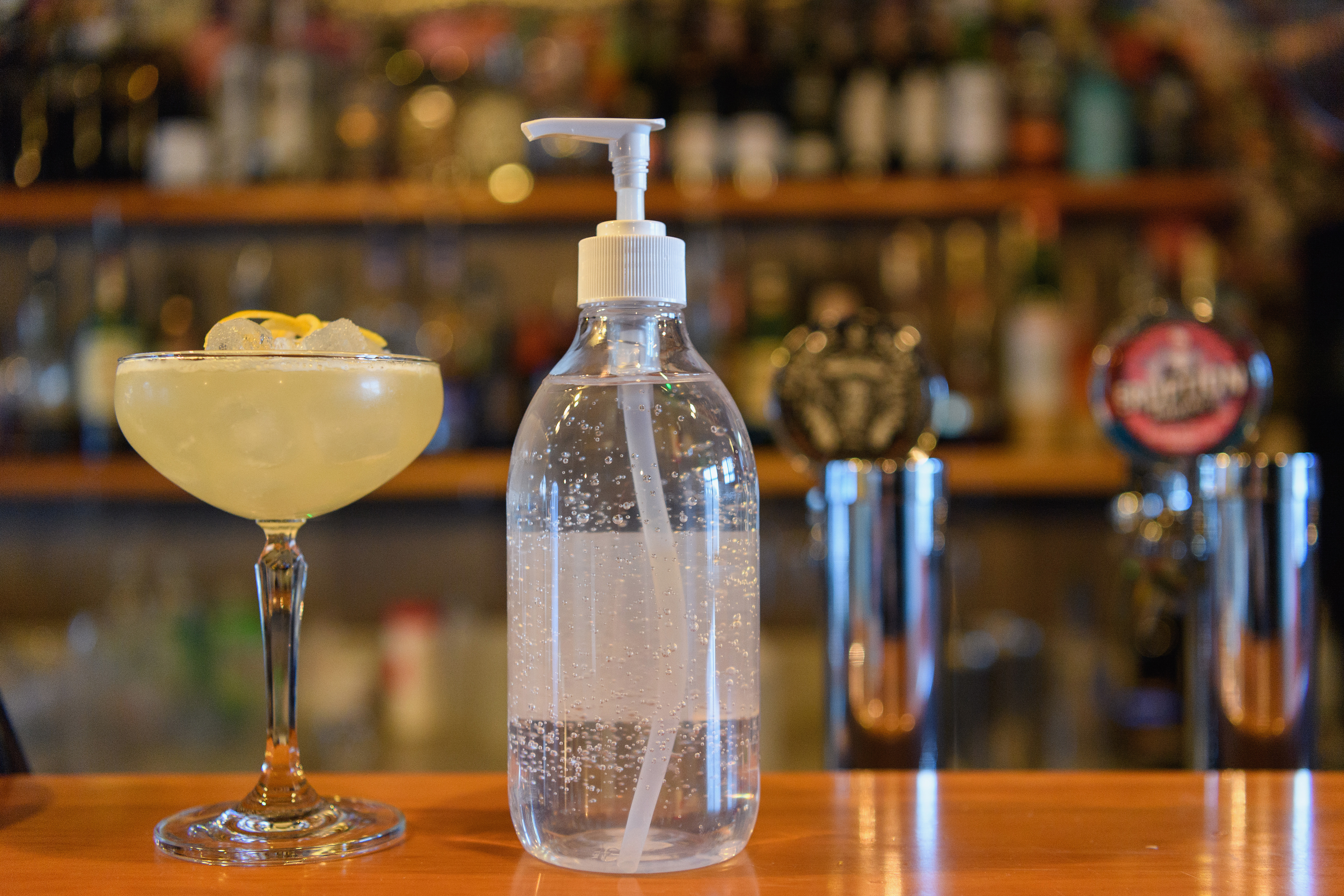 Hand sanitizer is seen between a cocktail and a beer tab at The Instiution bar in Christchurch, New Zealand, last week.