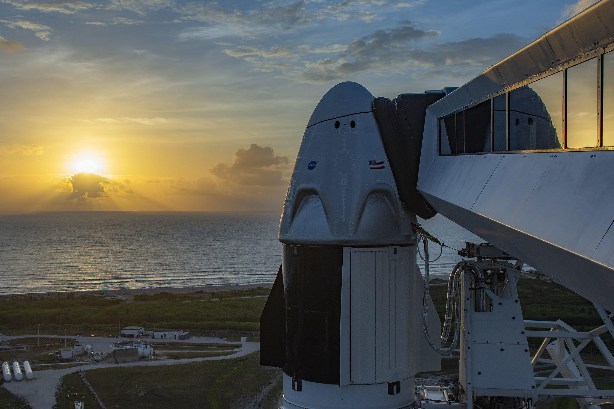 The Sun rises in the background over the water. In the foreground, the sleek gumdrop-shaped Crew Dragon sits atop a rocket connected to a walkway.