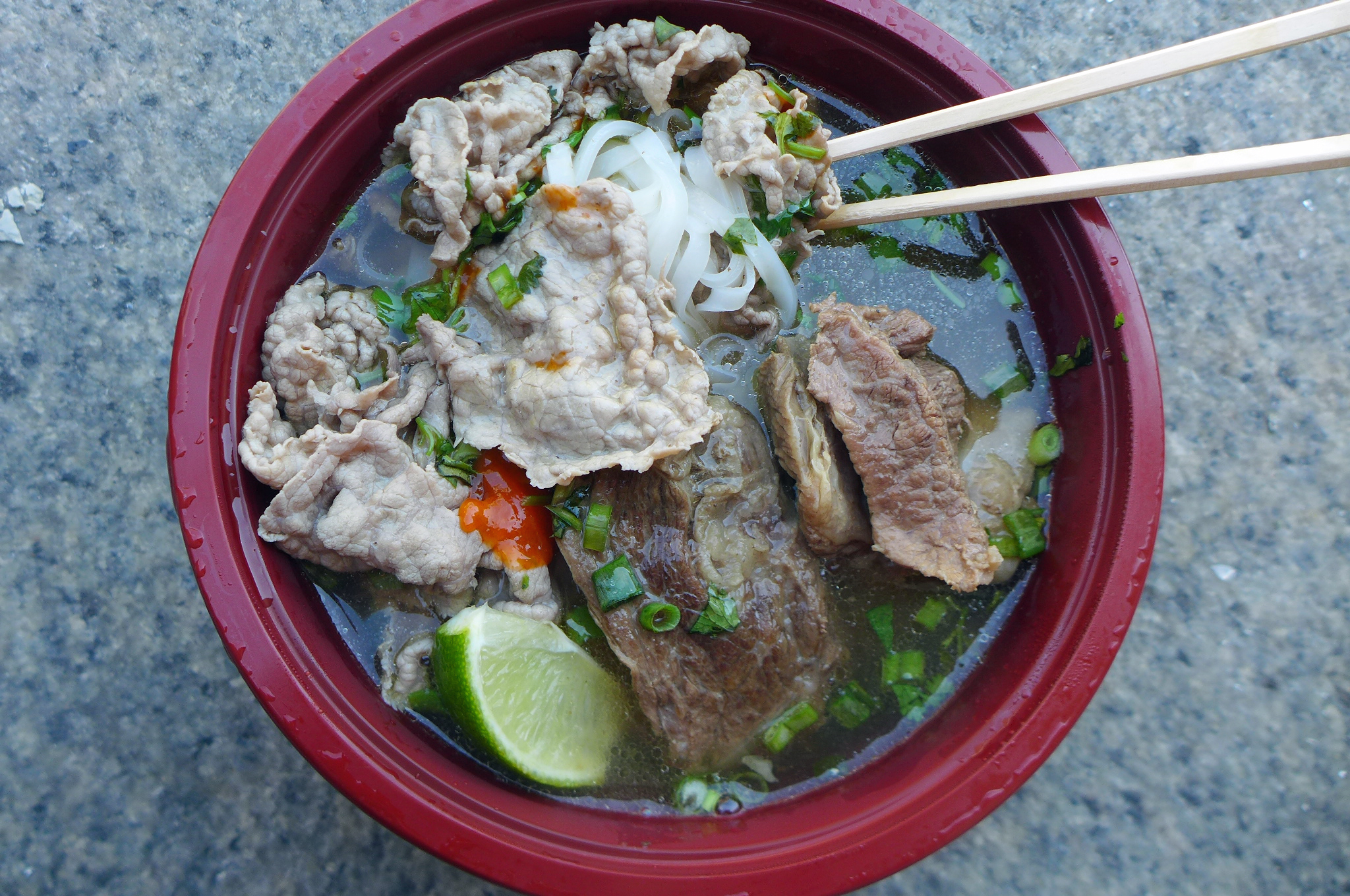 A bowl of soup with two types of beef and chopsticks thrust into the soup.