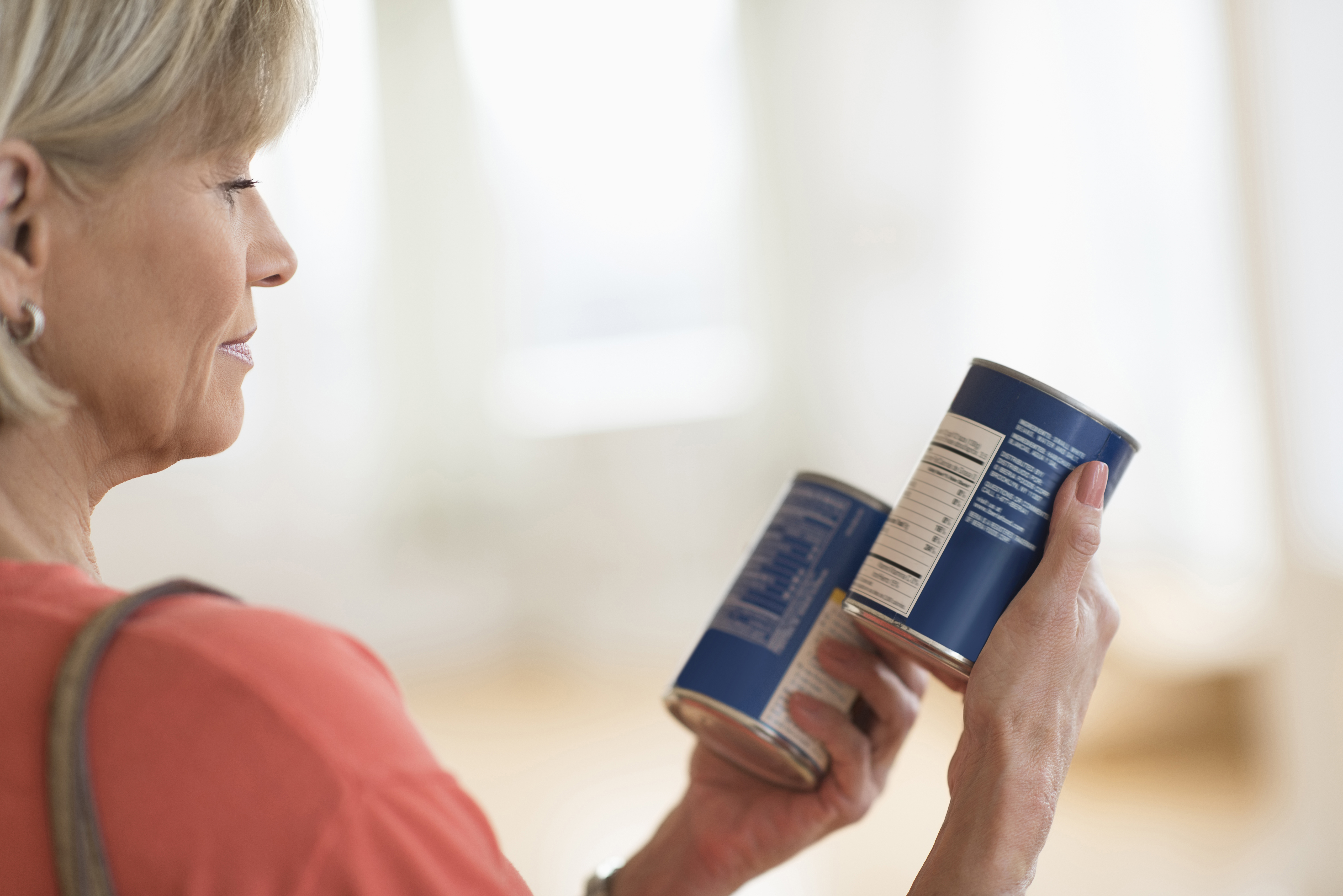 Woman comparing two cans' of food's labels.