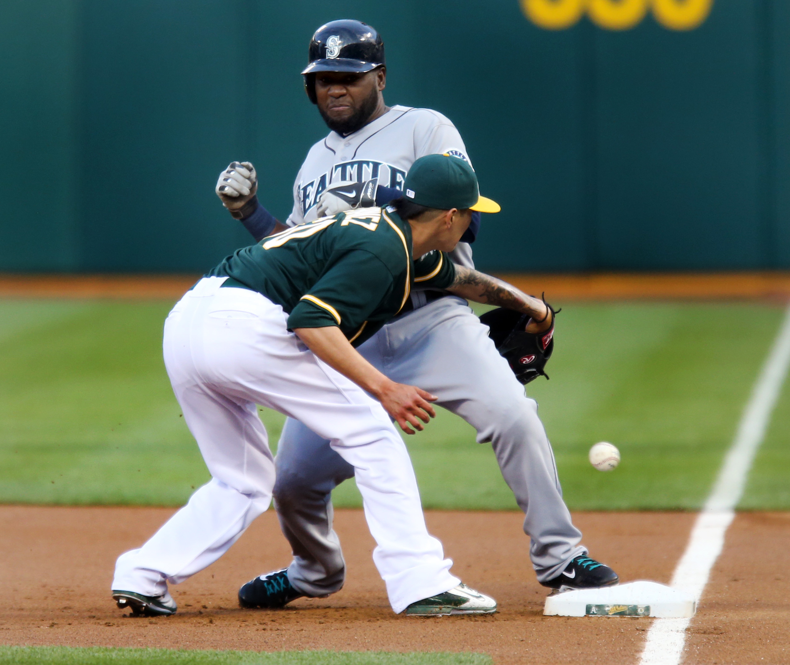 Oakland Athletics starting pitcher Jesse Chavez (60) fails to catch the throw at first base as Seattle Mariners' Abraham Almonte (36) takes advantage of the error and runs to second in the first inning of their MLB game at O.co Coliseum in Oakland, Calif.