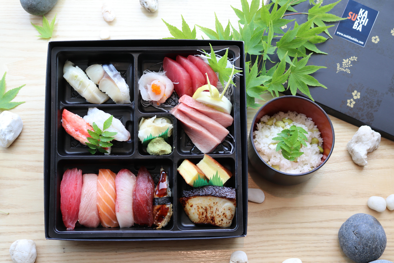 A bird's eye view of Sushi Kashiba's omakase box, with sashimi and sushi inside