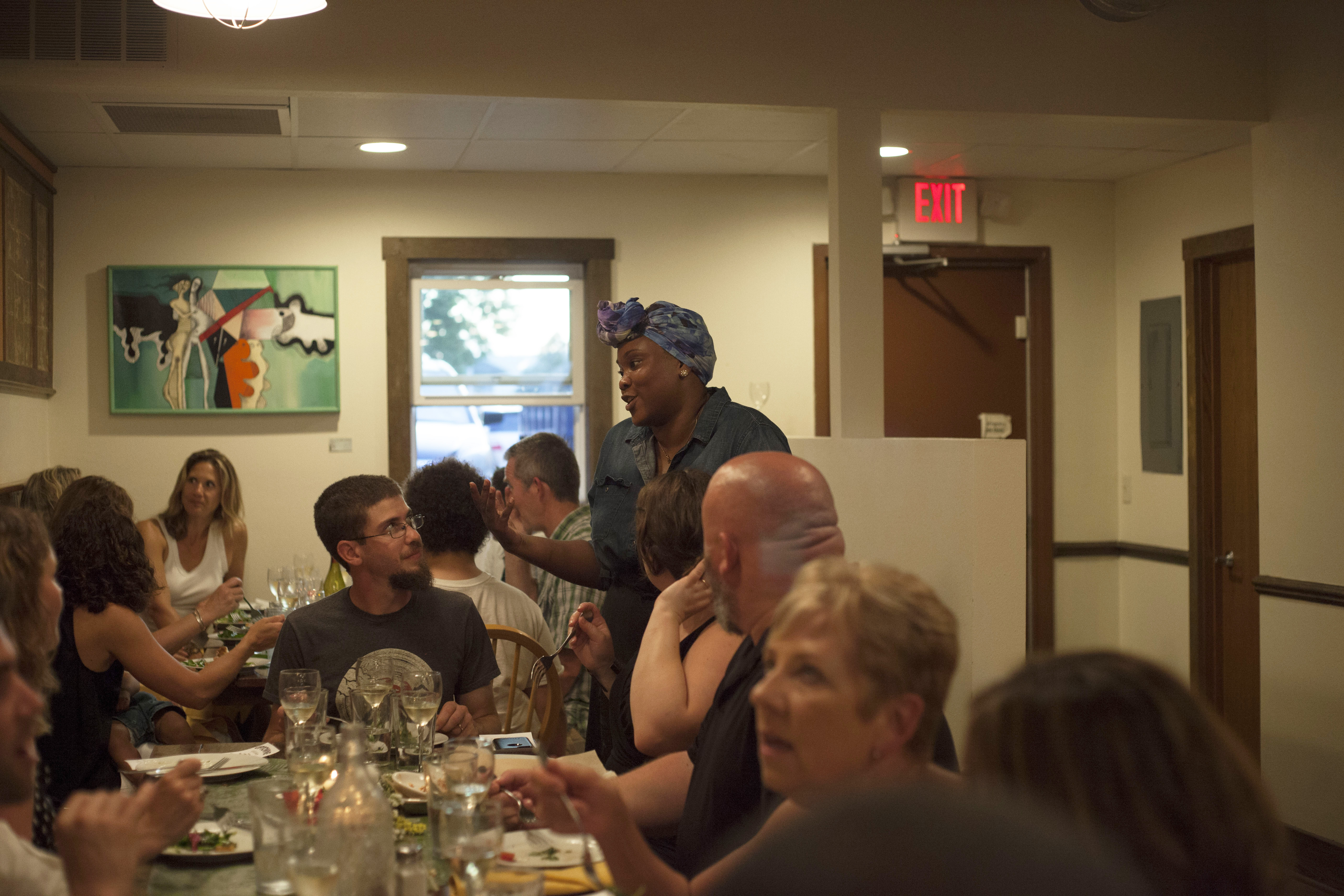 A woman, standing, talks with people seated at a dinner table.