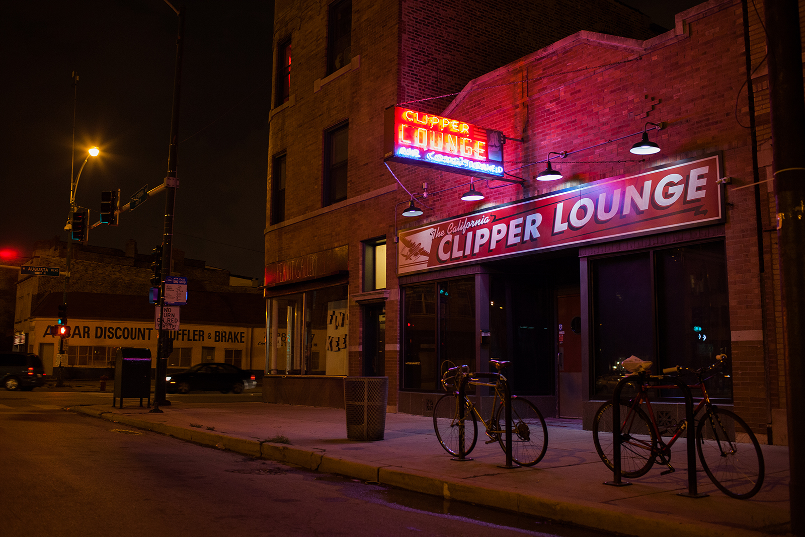 A night shot of a bar with a neon red sign and brick facade.