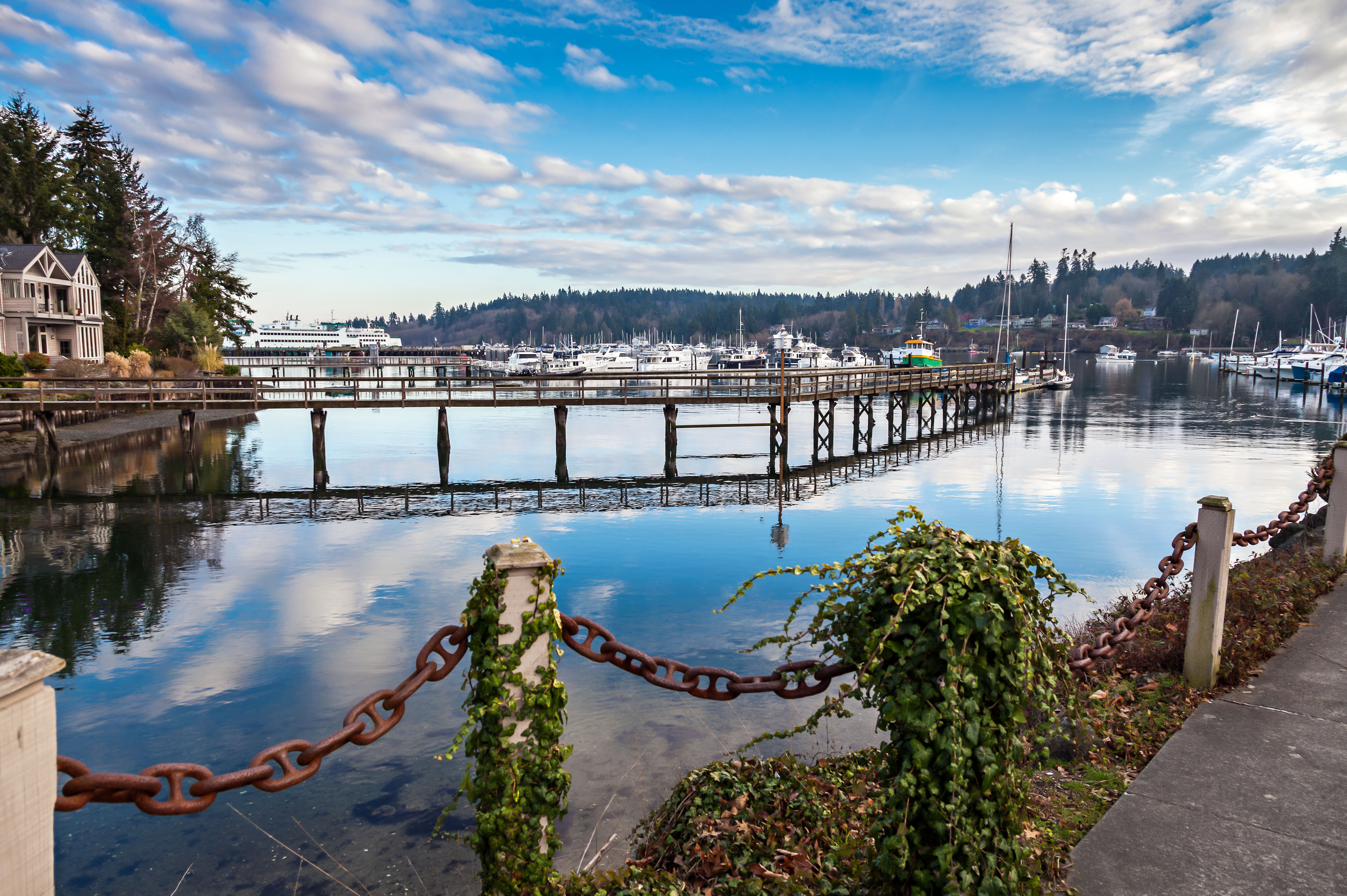 A view of Bainbridge Island, with a small bridge and bay in the foreground, and trees and mountains in the background