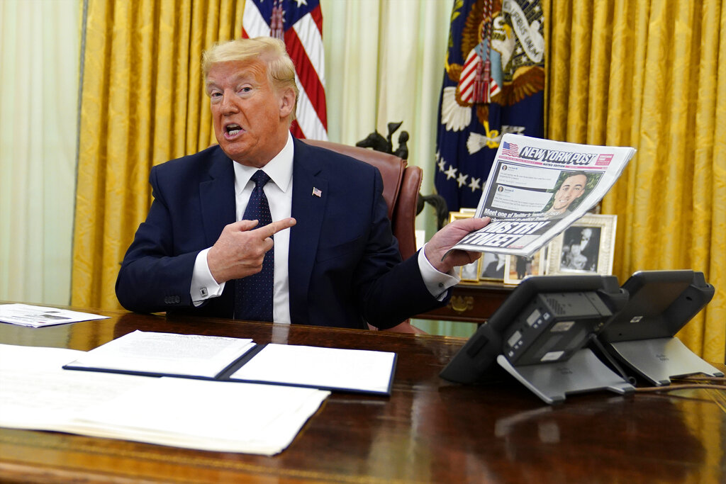 President Donald Trump holds up a copy of the New York Post as speaks before signing an executive order aimed at curbing protections for social media giants.