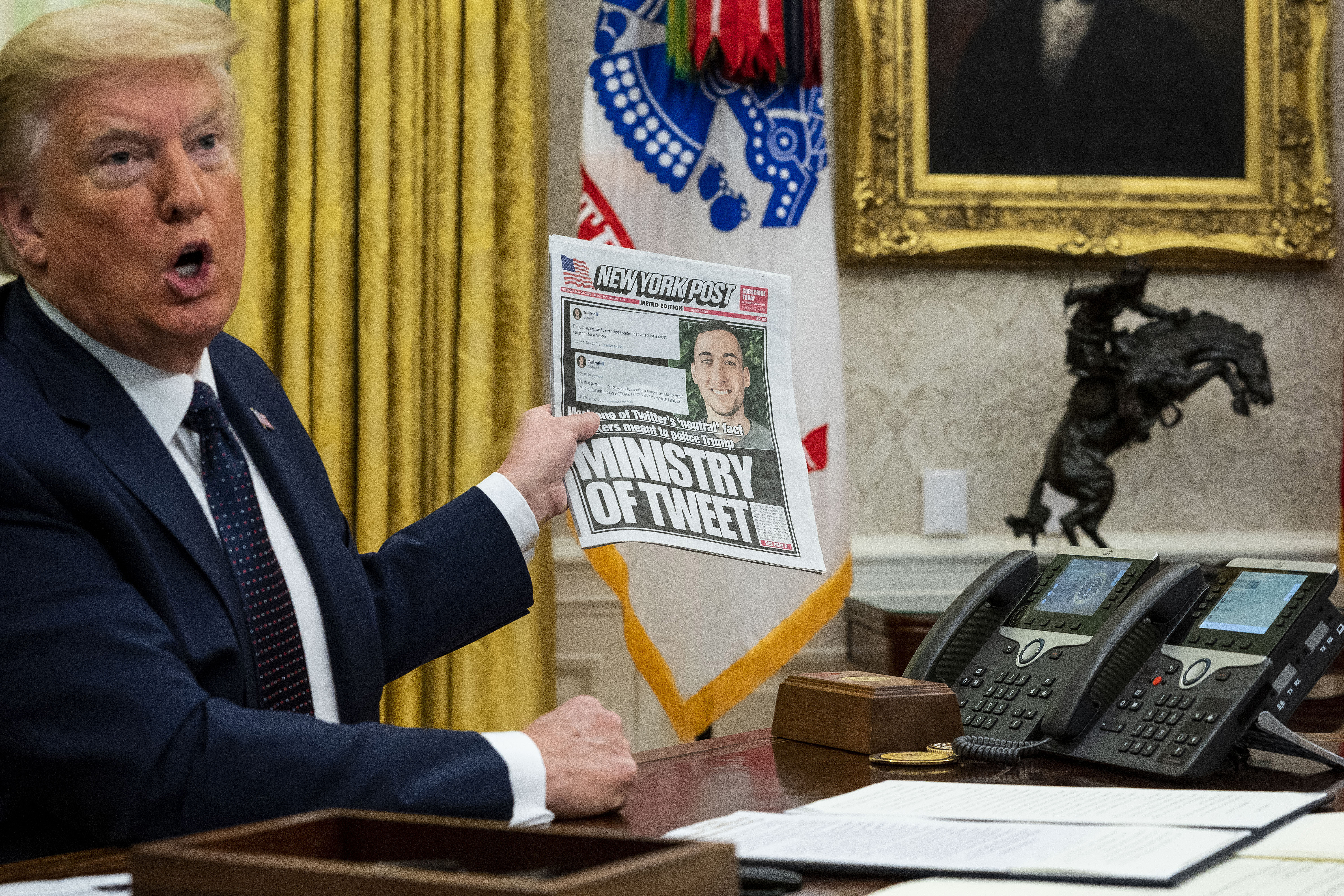 Trump sits at his desk holding up a copy of the New York Post.