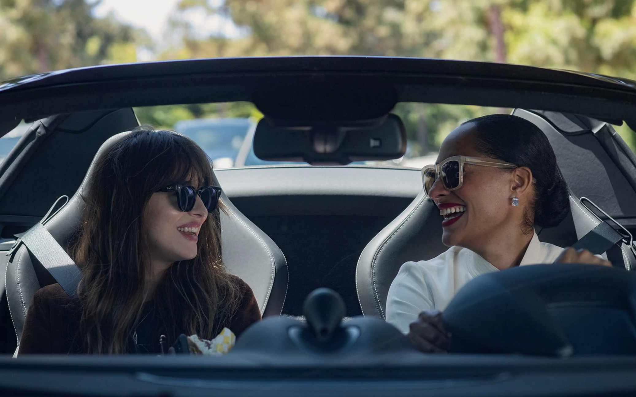 Two women smile at one another in a car.
