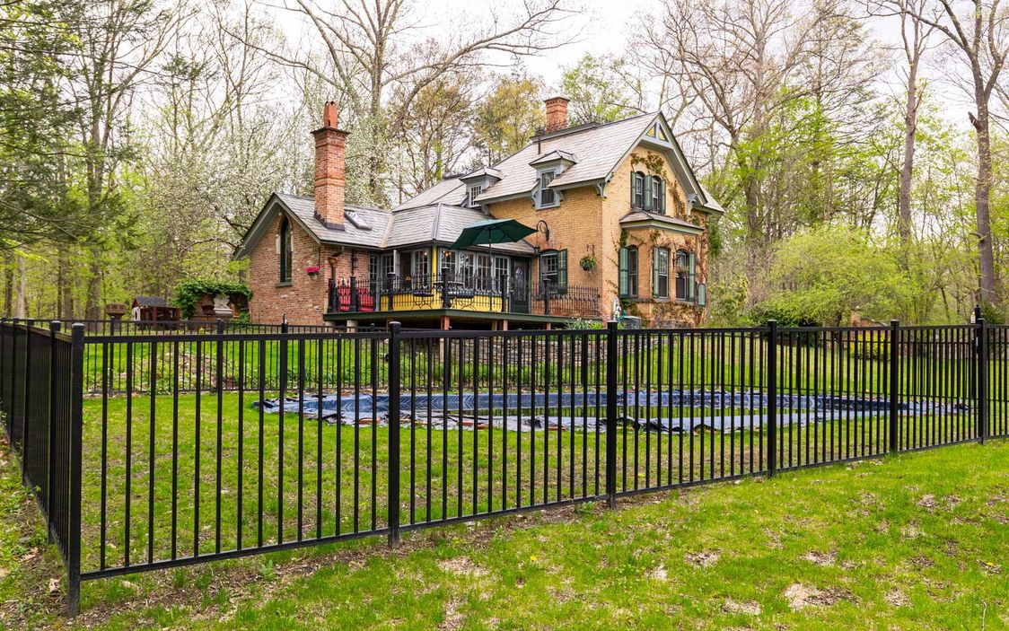 A two-story brick building sits behind an iron gate in a forested and green grass area.