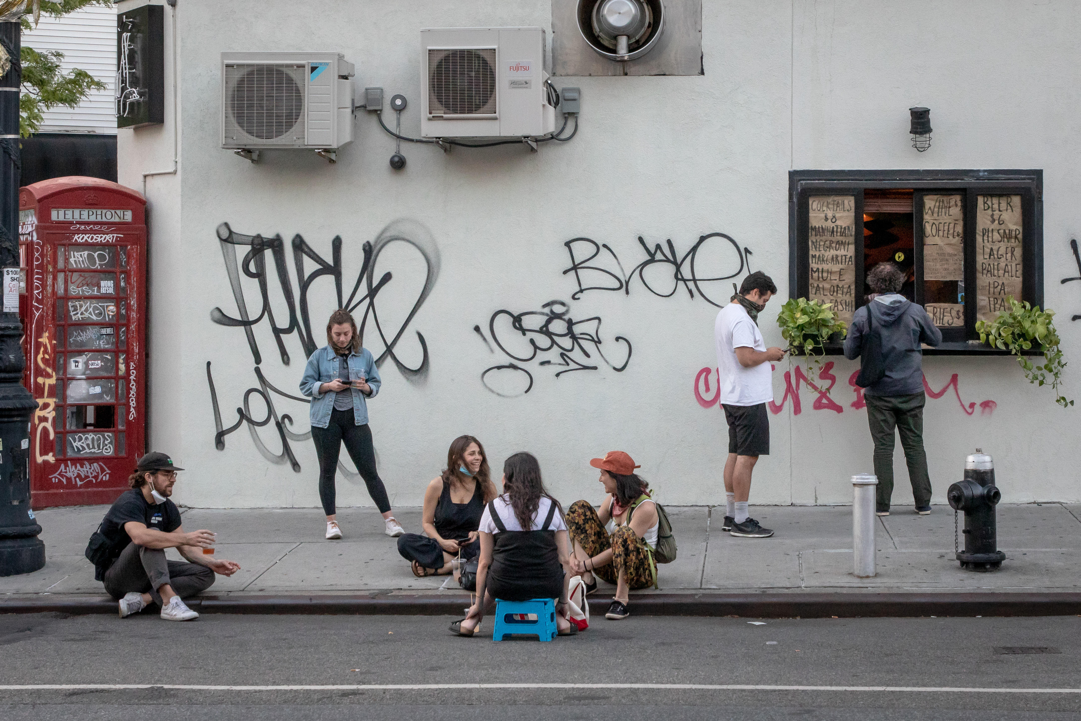 Patrons sit on the sidewalk outside a business with a takeout window