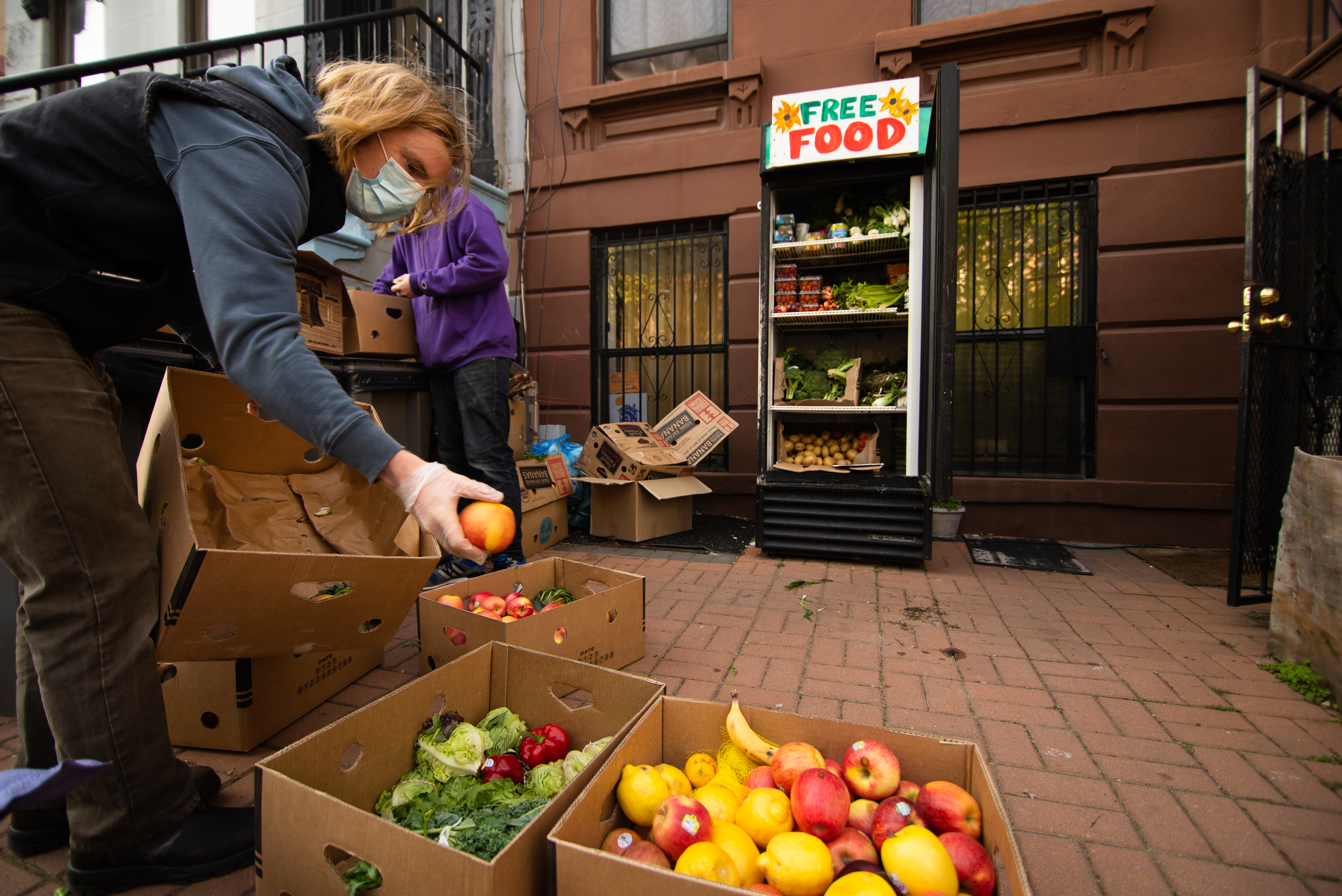 """A glass-front fridge stocked with produce with a sign that says """"free food"""" in hand-drawn letters. A person with blonde hair is reaching into a cardboard box filled with apples."""