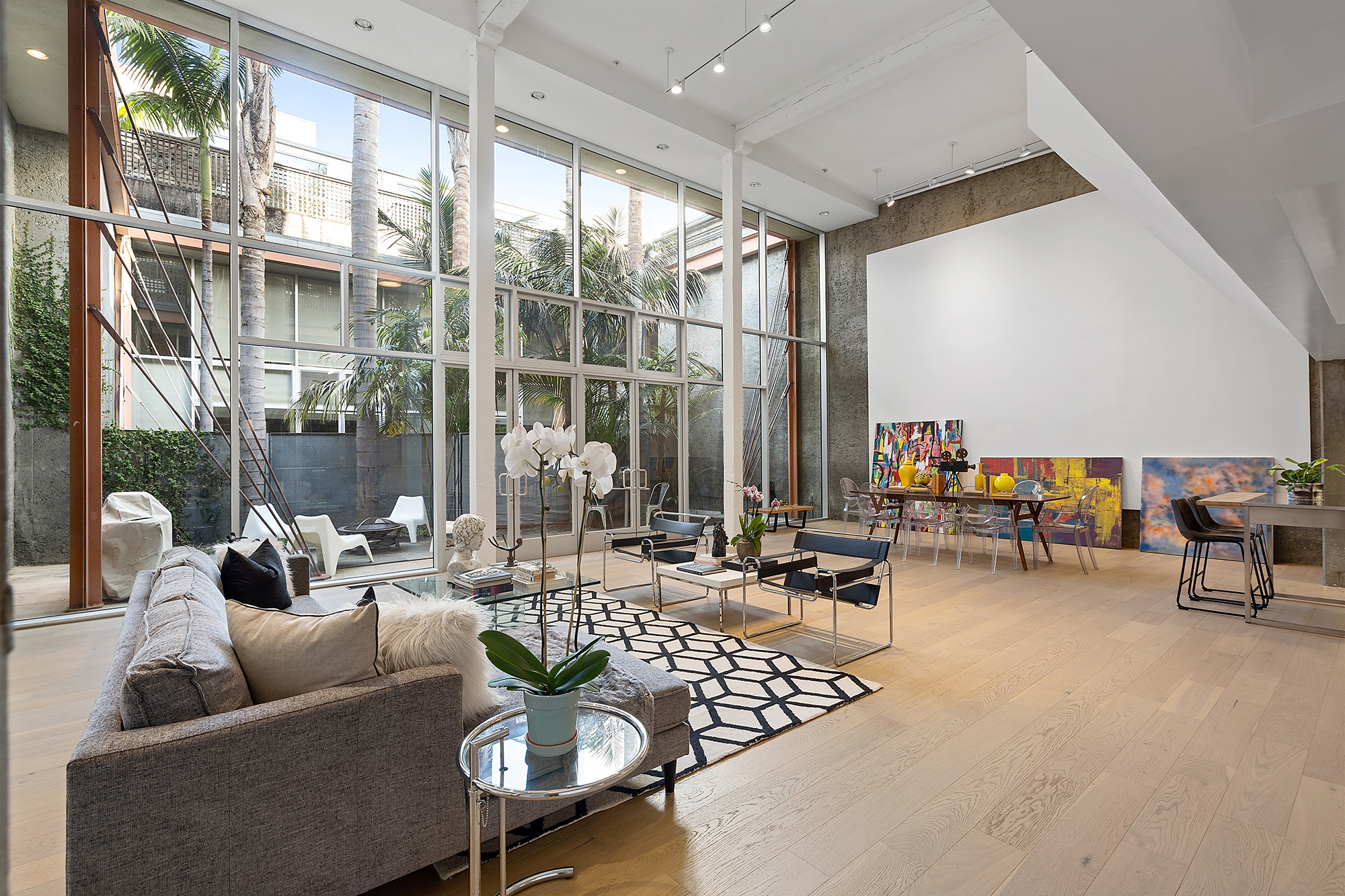 A huge living room with a wall of windows, a white canvas on a concrete wall, and track lighting on the ceiling.