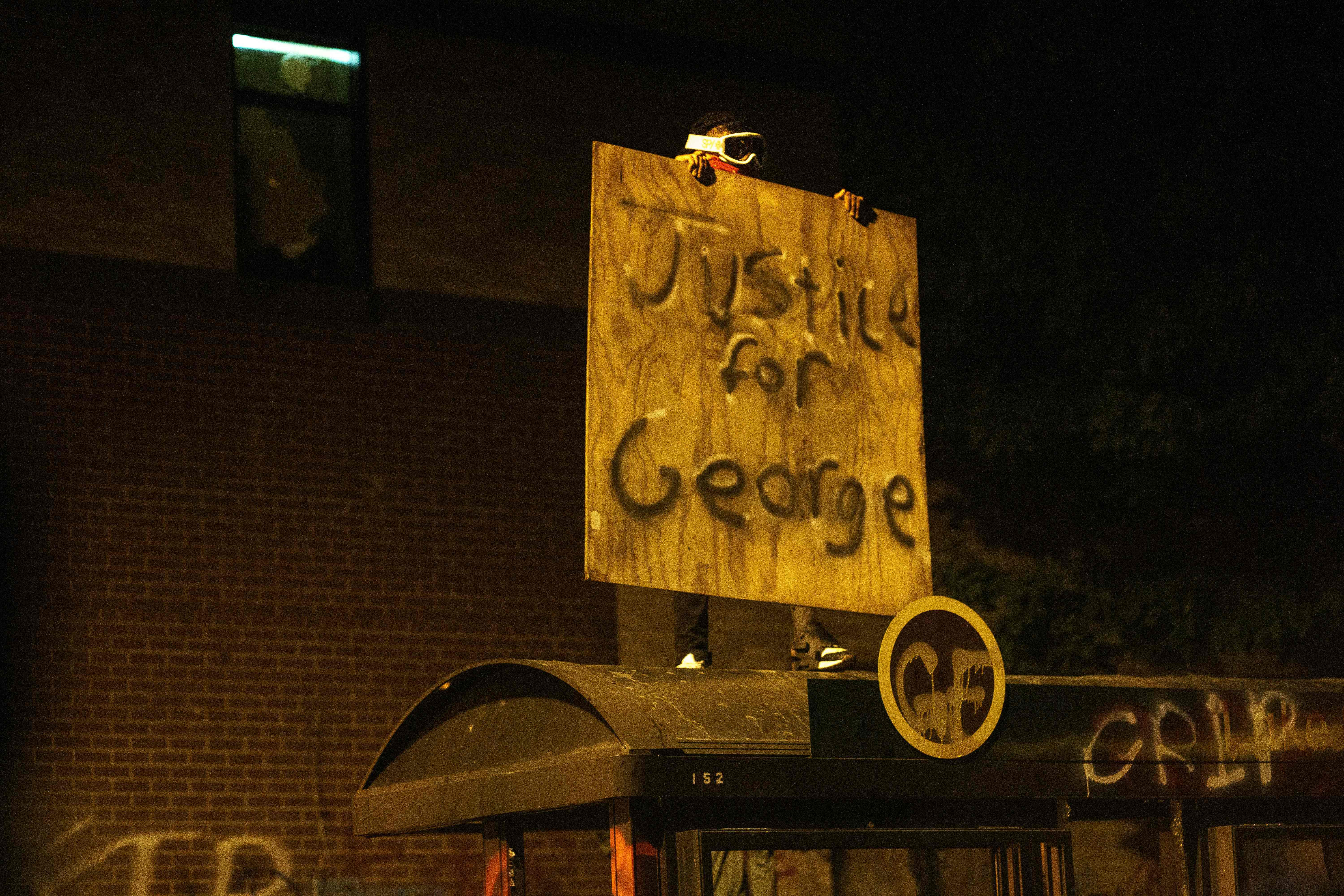 """A protester stands atop a bus stop, holding a piece of plywood spray-painted with """"Justice for George"""" in black, at night."""