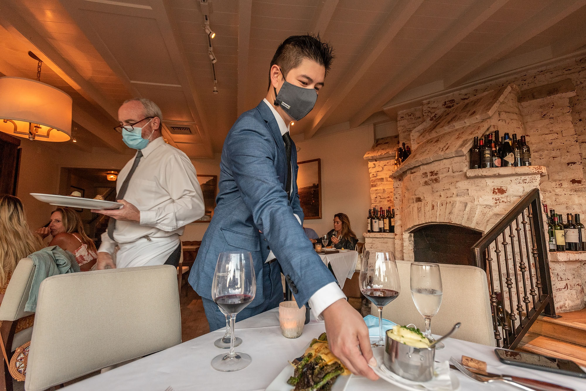 Servers at Selanne Steak Tavern place dishes at table in Laguna Beach on the restaurant's first night of reopenings its dining room