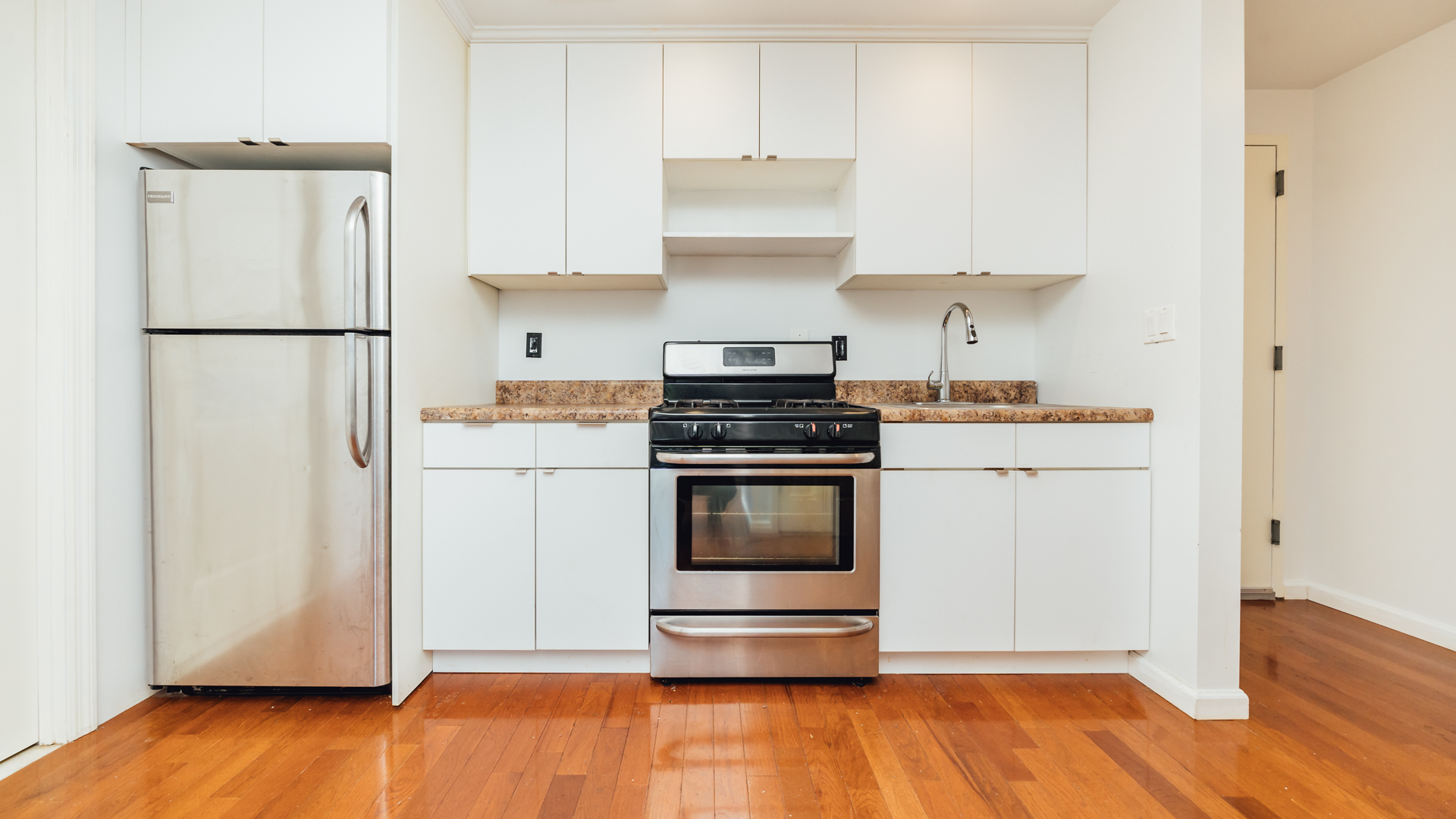 A kitchen with white cabinetry and hardwood floors.