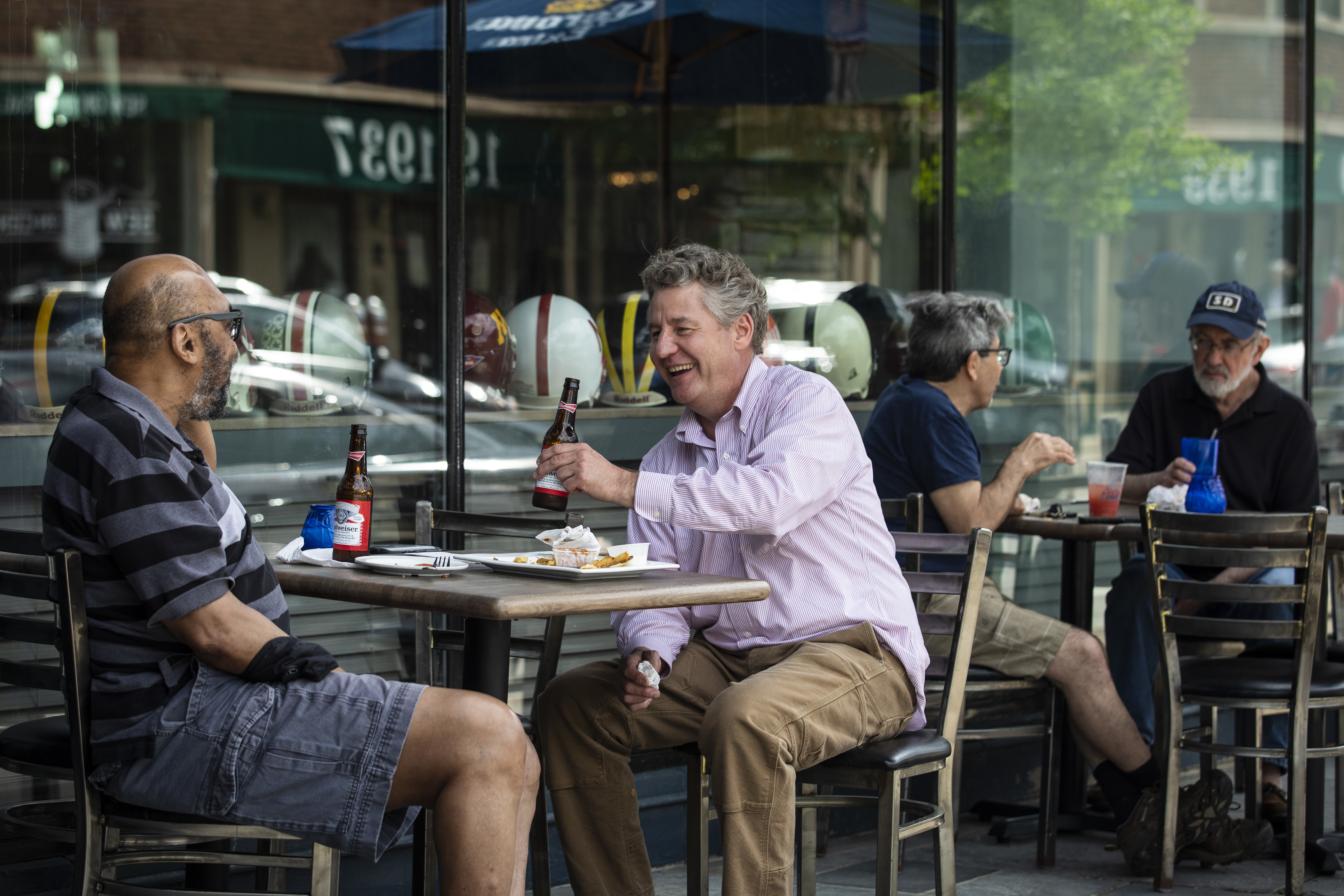 Bill Luby (center), 54, laughs with his friend, Calvin Grant, 53, both from Evanston, as they eat and drink together on the patio at Bluestone, 1932 Central St. in Evanston, Friday afternoon, May 29, 2020. Illinois entered Phase 3 of Gov. J.B. Pritzker's reopening plan for the state Friday, allowing many nonessential businesses to reopen with guidelines for social distancing and capacity limits.