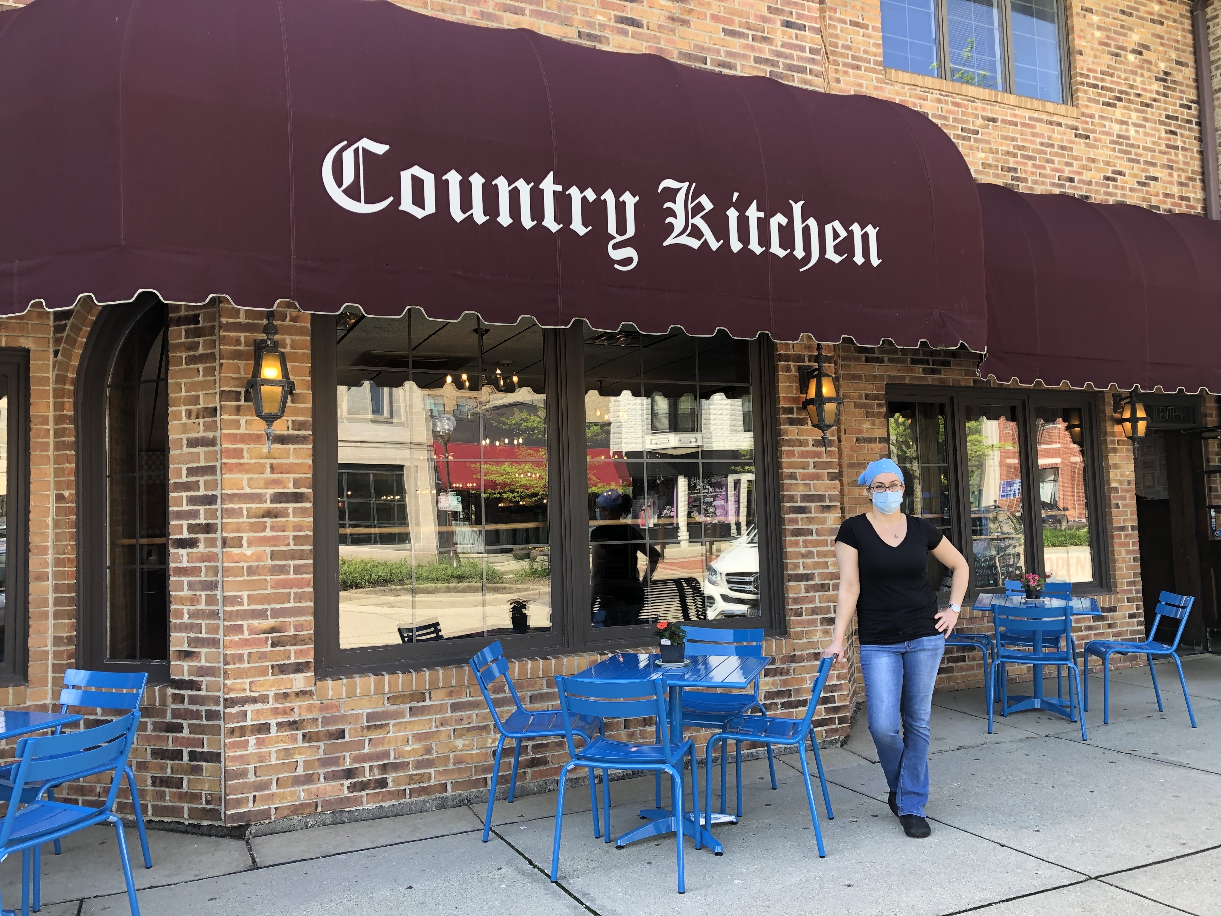 "On Friday, Ruby Iliopoulos, manager of Country Kitchen, a Highland Park institution, was presiding over new, blue outdoor dining tables while the big back lot was being repaved so the restaurant can erect a tent for even more outdoor dining. ""We're adapting for this next step, starting back up little by little,"" she said."