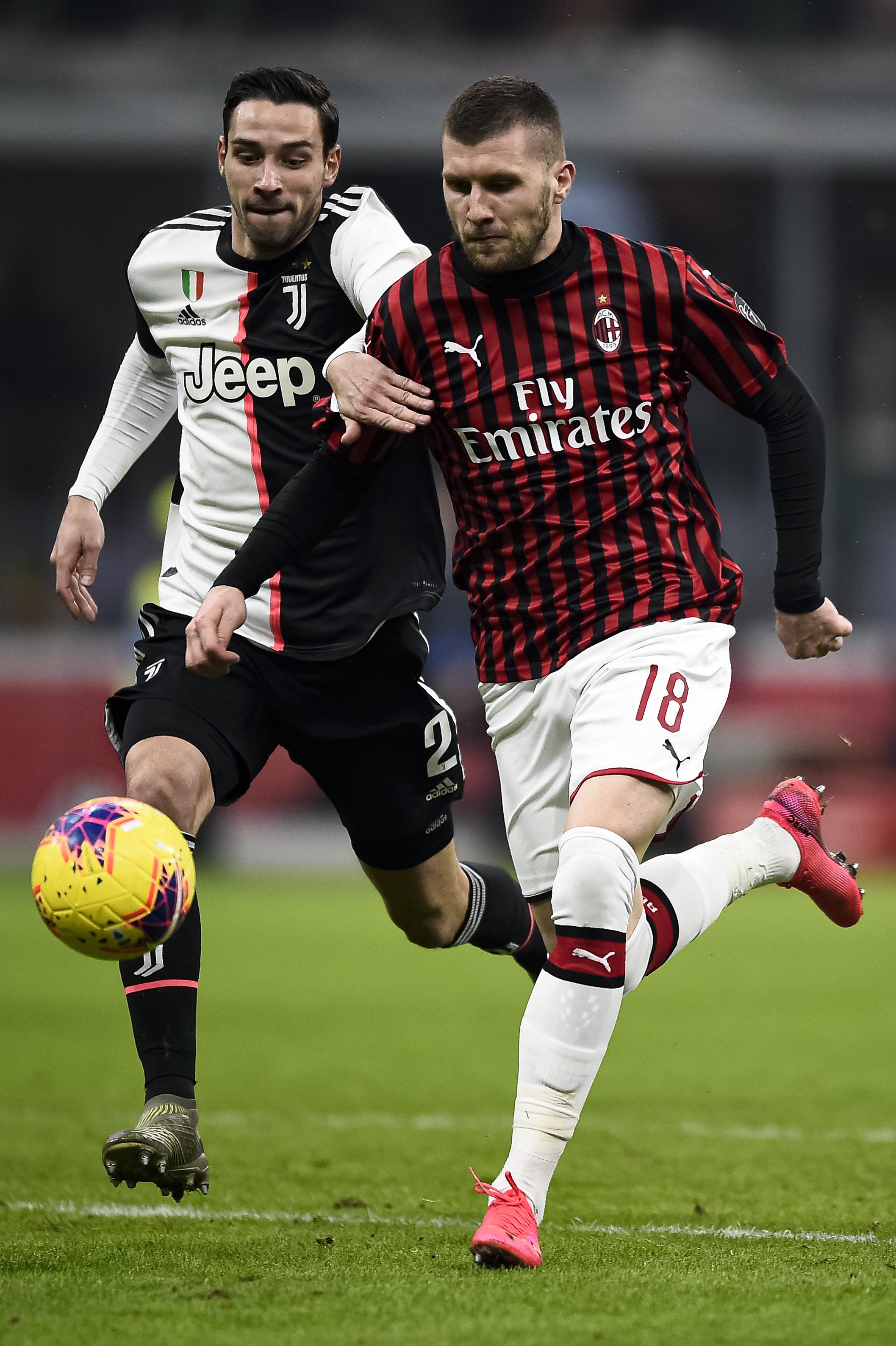Ante Rebic (R) of AC Milan is challenged by Mattia De...