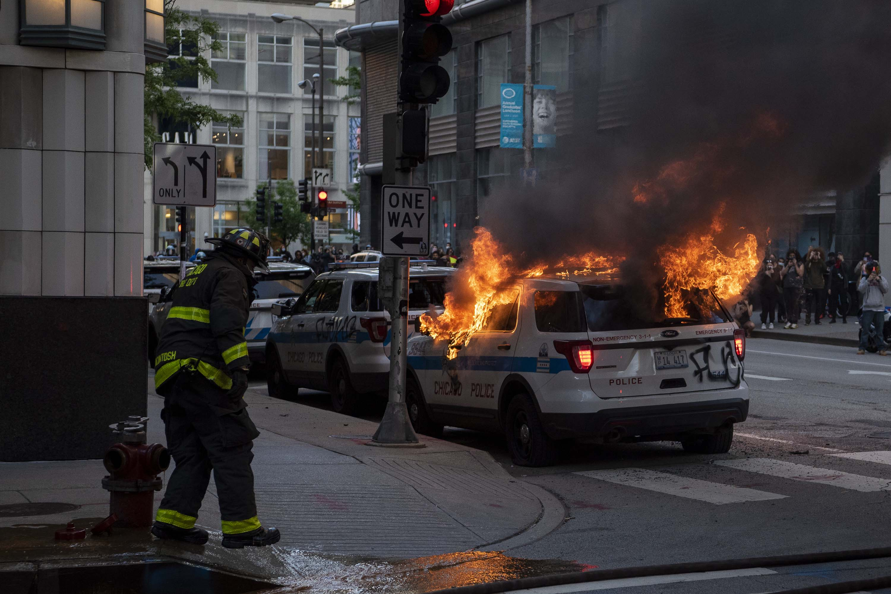 Chicago fire department respond to a Police vehicle set ablaze during a protest for George Floyd, Saturday, May 30, 2020.