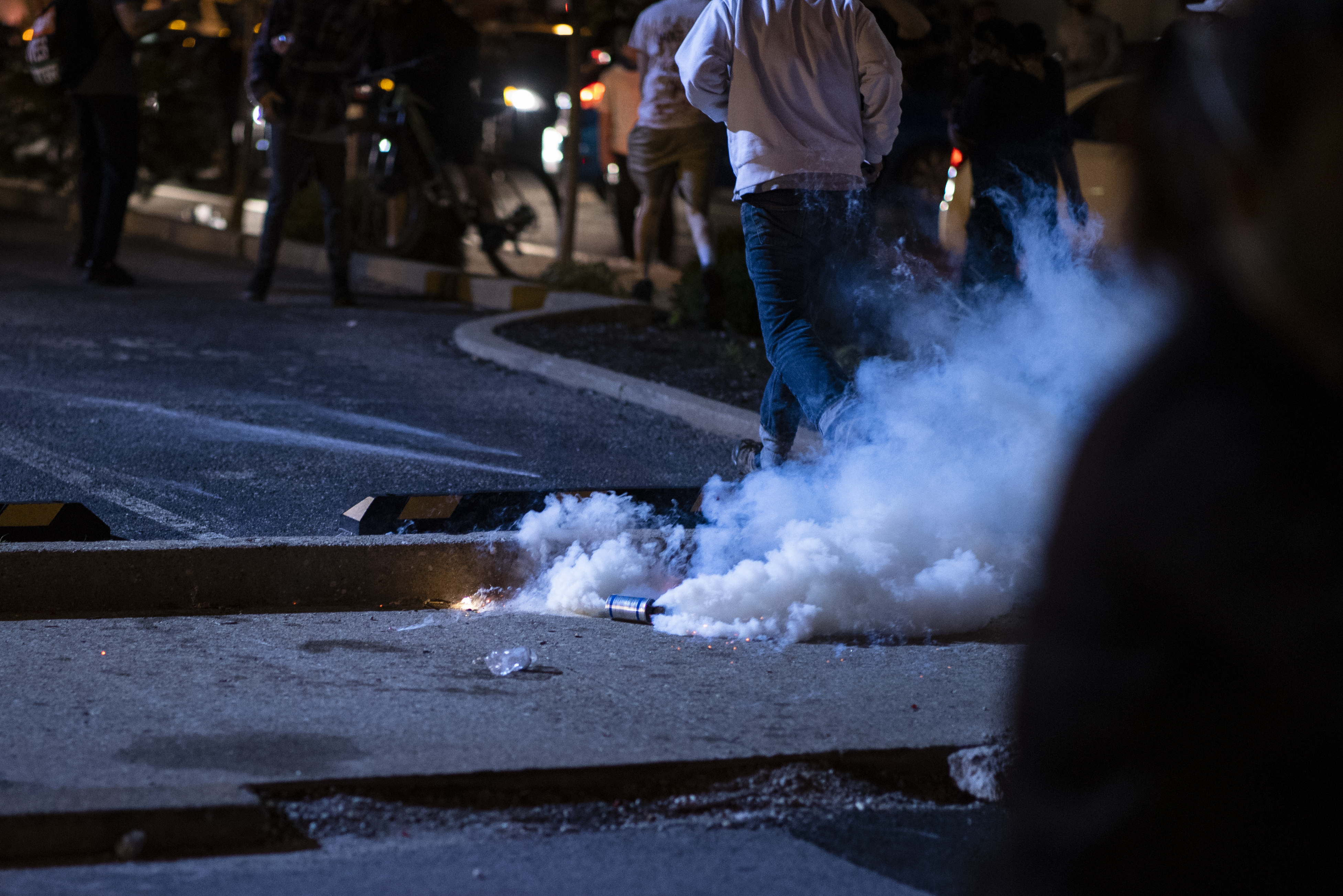 A man in a gray sweatshirt and blue jeans runs away from an active tear gas canister thrown by police on the street in Louisville.