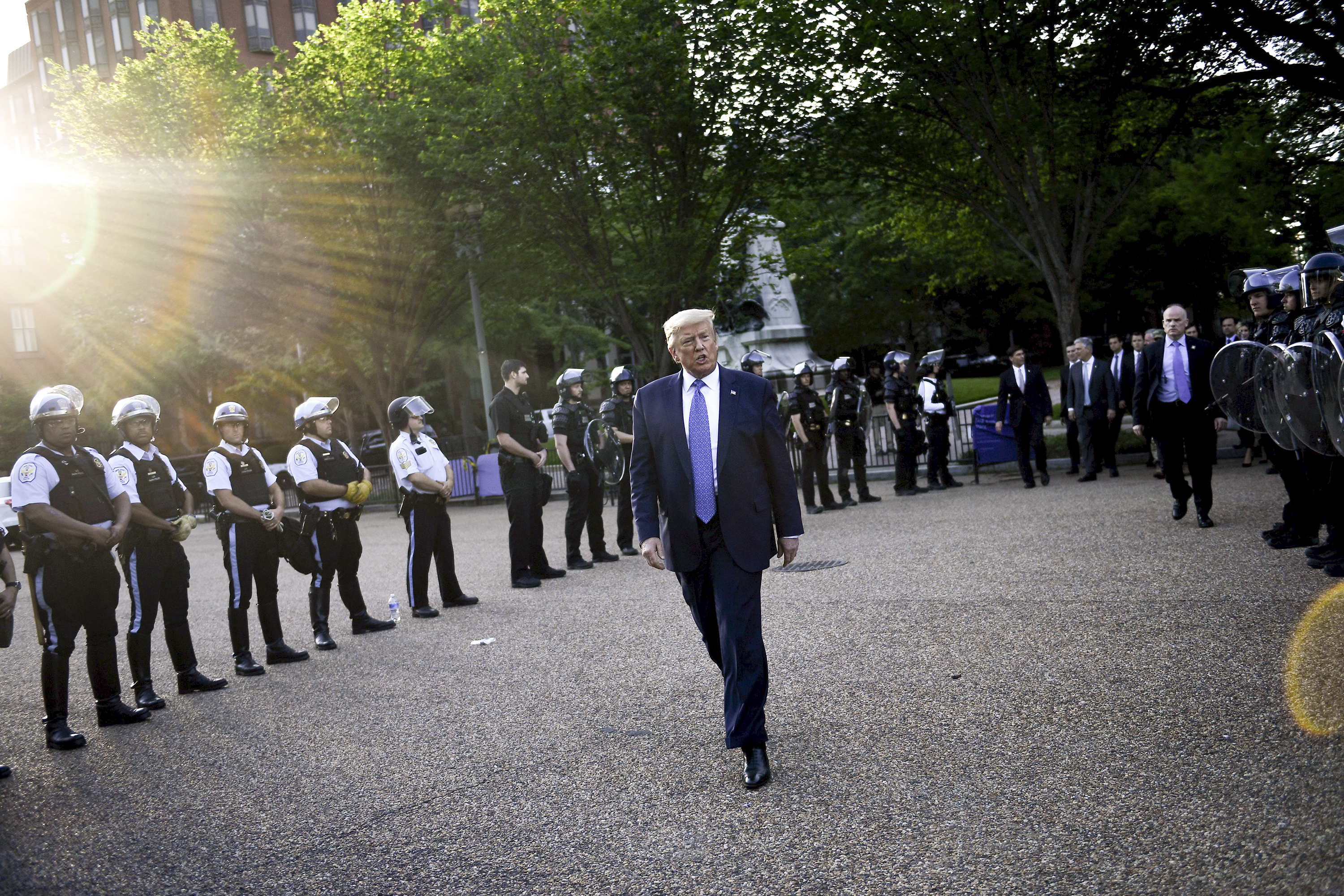 President Donald Trump, in a navy suit and blue tie, walks between two columns of police officers clad in riot gear. The officers are in tight ranks, creating a path of protection for the president.