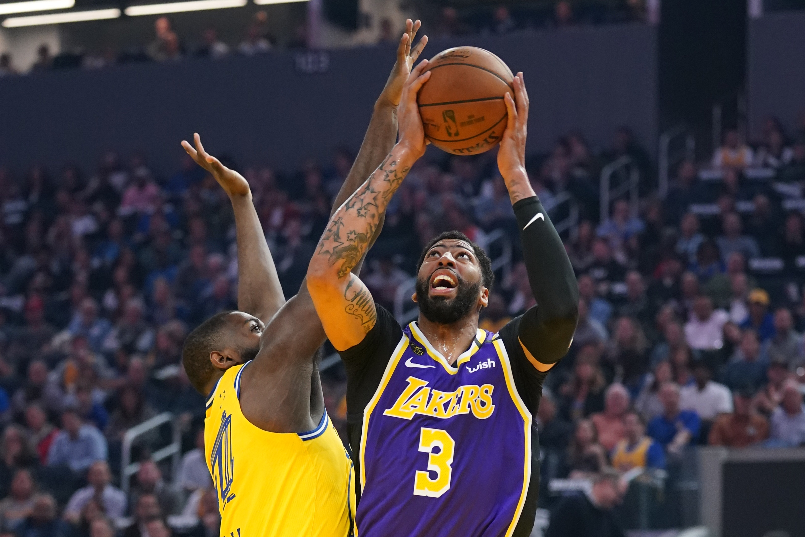 Los Angeles Lakers forward Anthony Davis shoots the basketball against Golden State Warriors forward Eric Paschall during the first quarter at Chase Center.