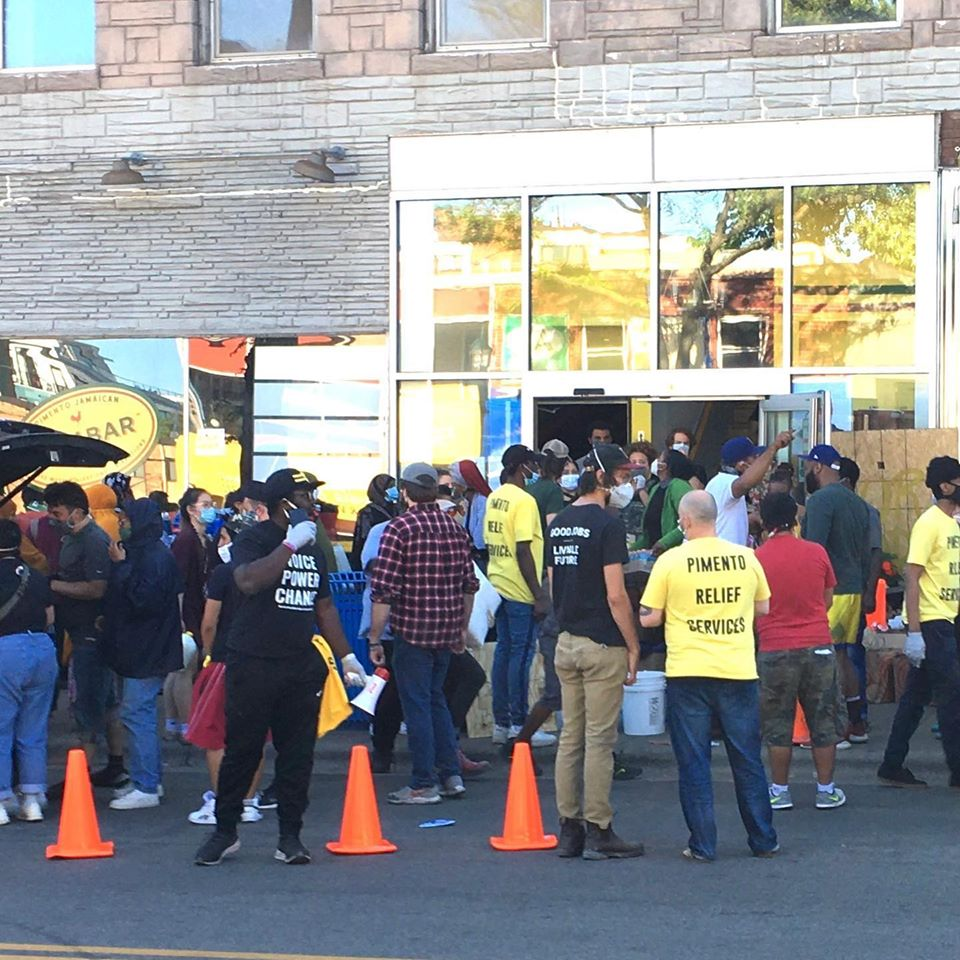 A bustling storefront with people, some in yellow t-shirts that read Pimento Relief Services