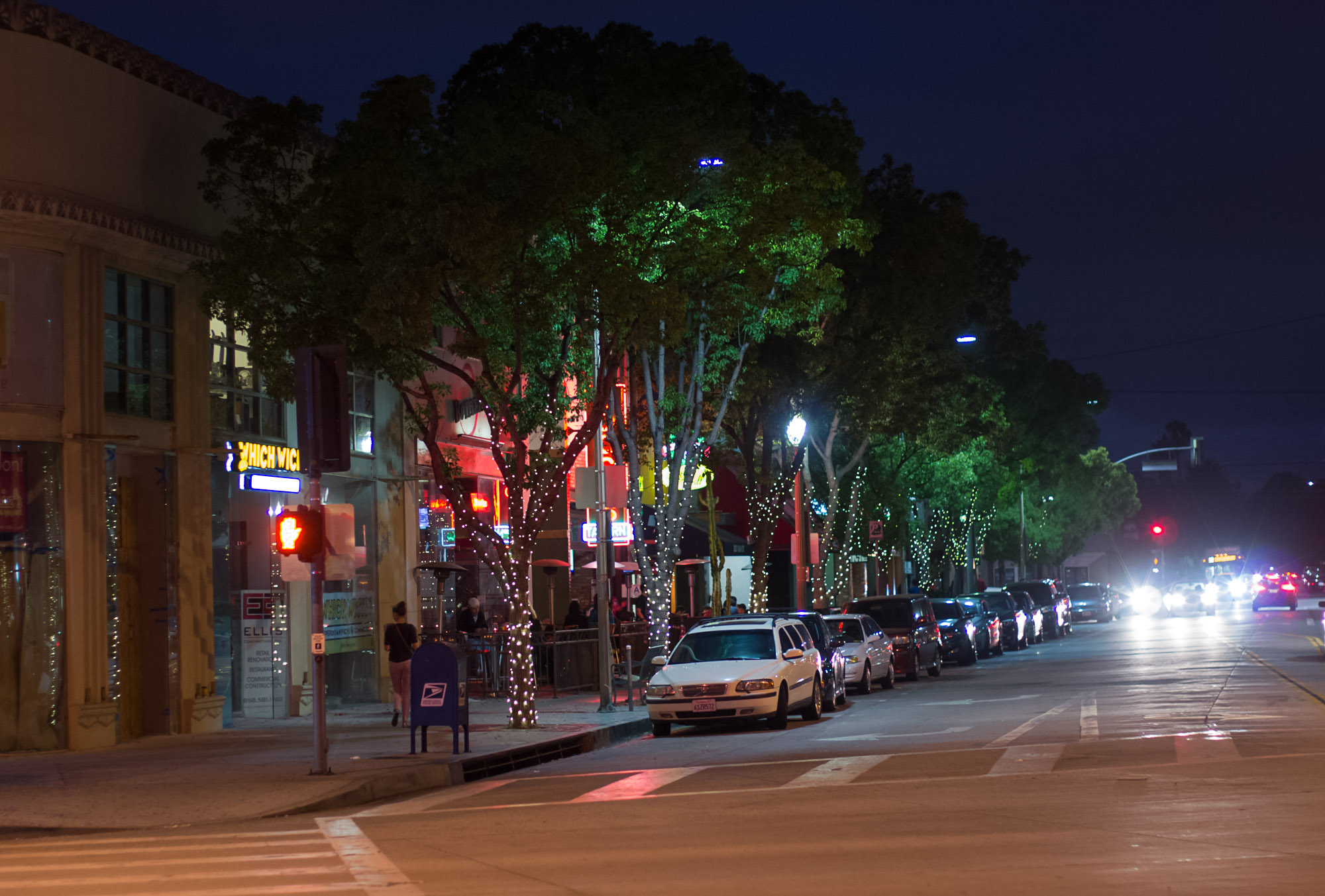 An evening exterior shot of a street with lights and patio diners.